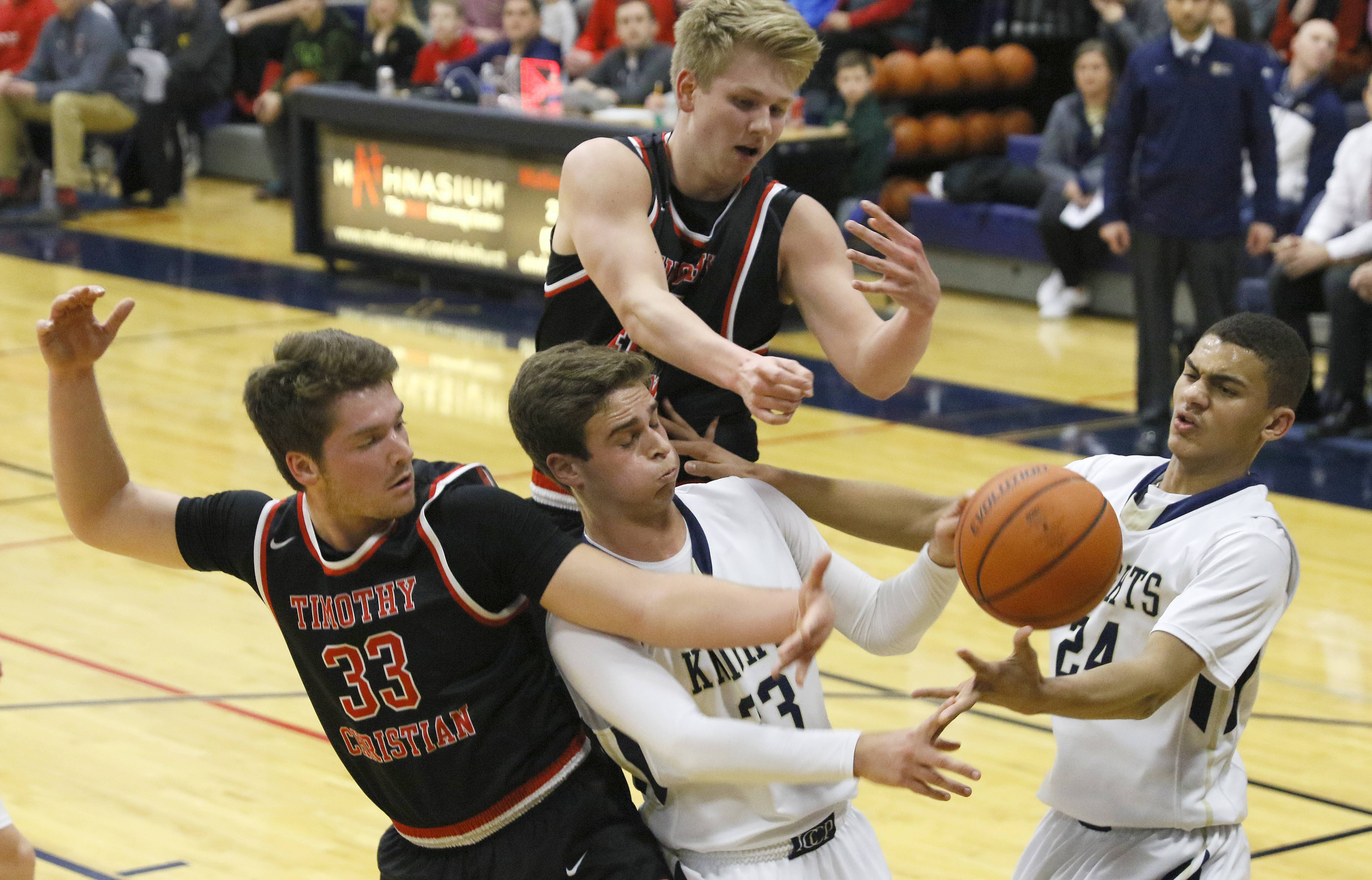Timothy Christian players Brandon Orange and Joey Davidson (33) battle for a loose ball with IC Catholic Prep's Tony Gaudio and Amari Reed (24) during the Class 2A boys basketball regional final in Elmhurst.