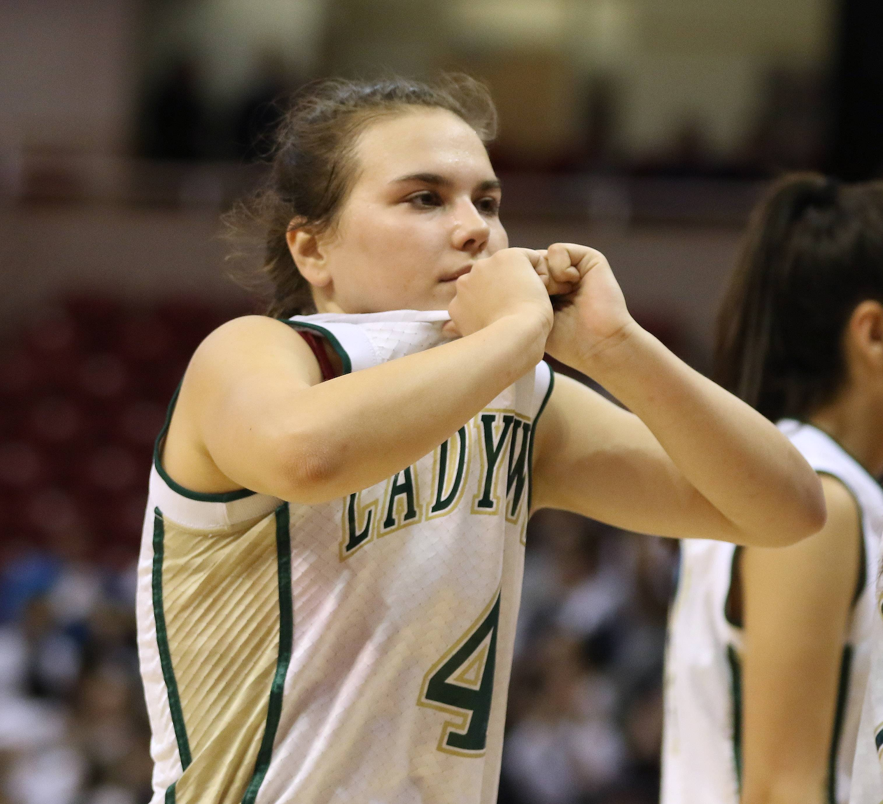 St. Edward's Maddie Spagnola walks off the floor after the Green Wave lost to Bloomington Central Catholic during the Class 2A state semifinal girls basketball game Friday in Normal.