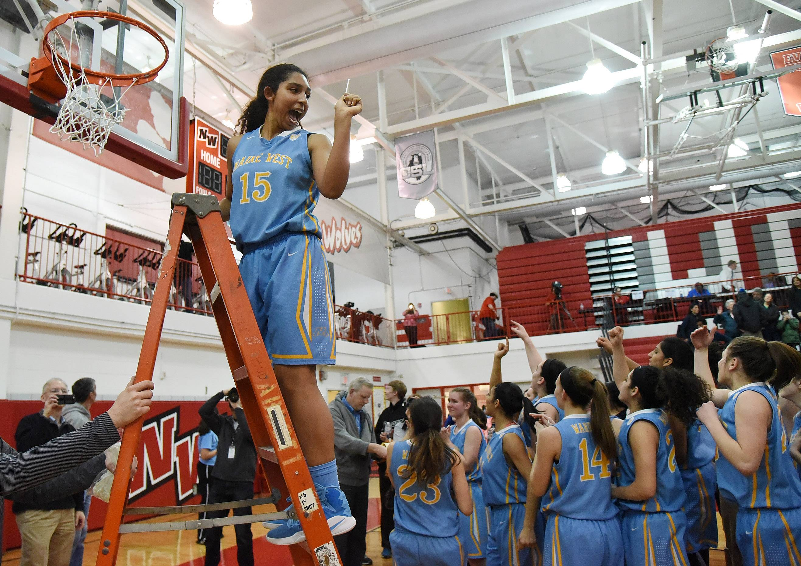 Rachel Kent cuts down a piece of the net after Maine West's victory over  Evanston in the Class 4A sectional final at Niles West on Thursday.