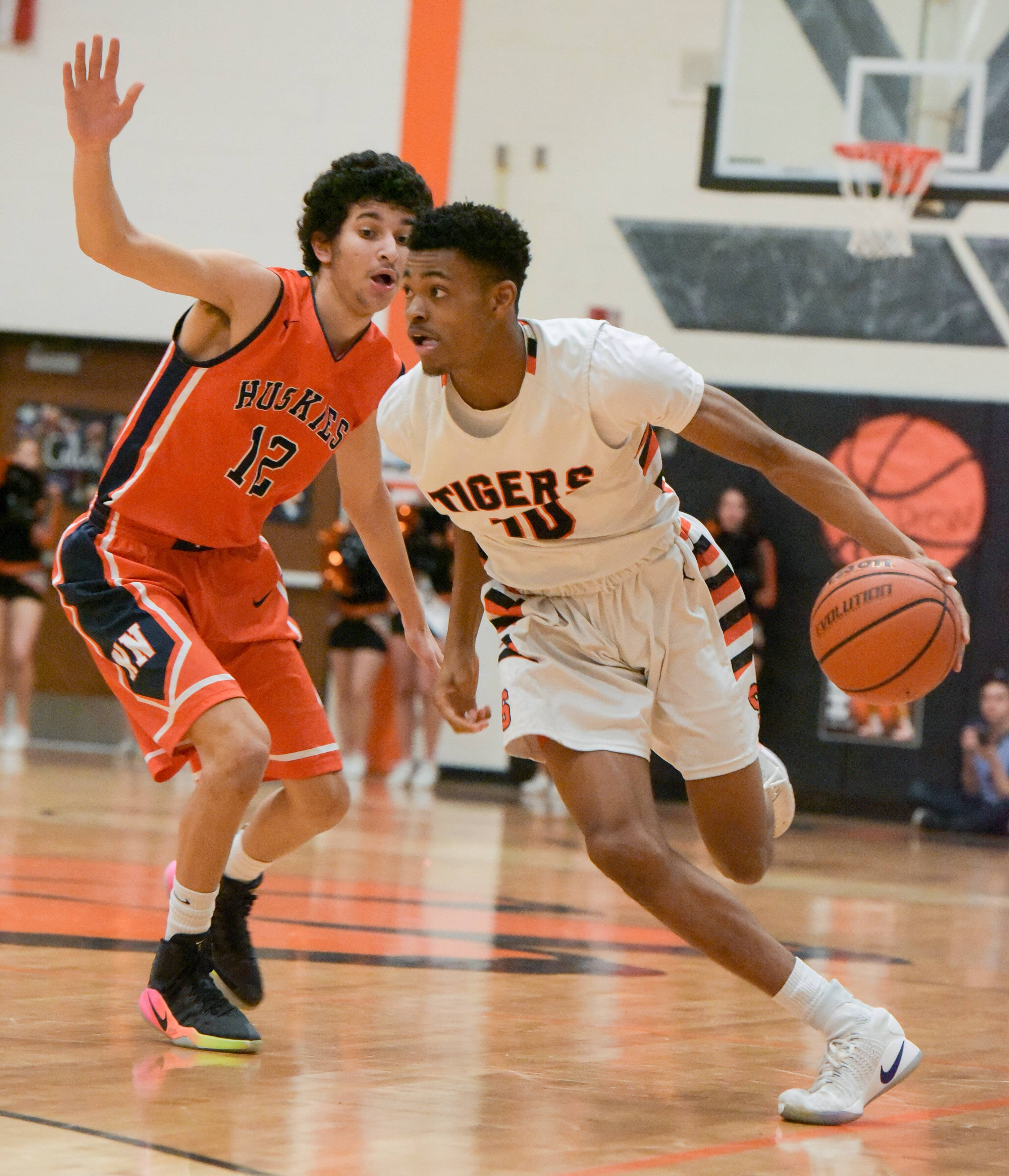 Wheaton Warrenville South's Dillon Durrett drives around Naperville North's Youcef Merabet during boys varsity basketball Wednesday in Wheaton.