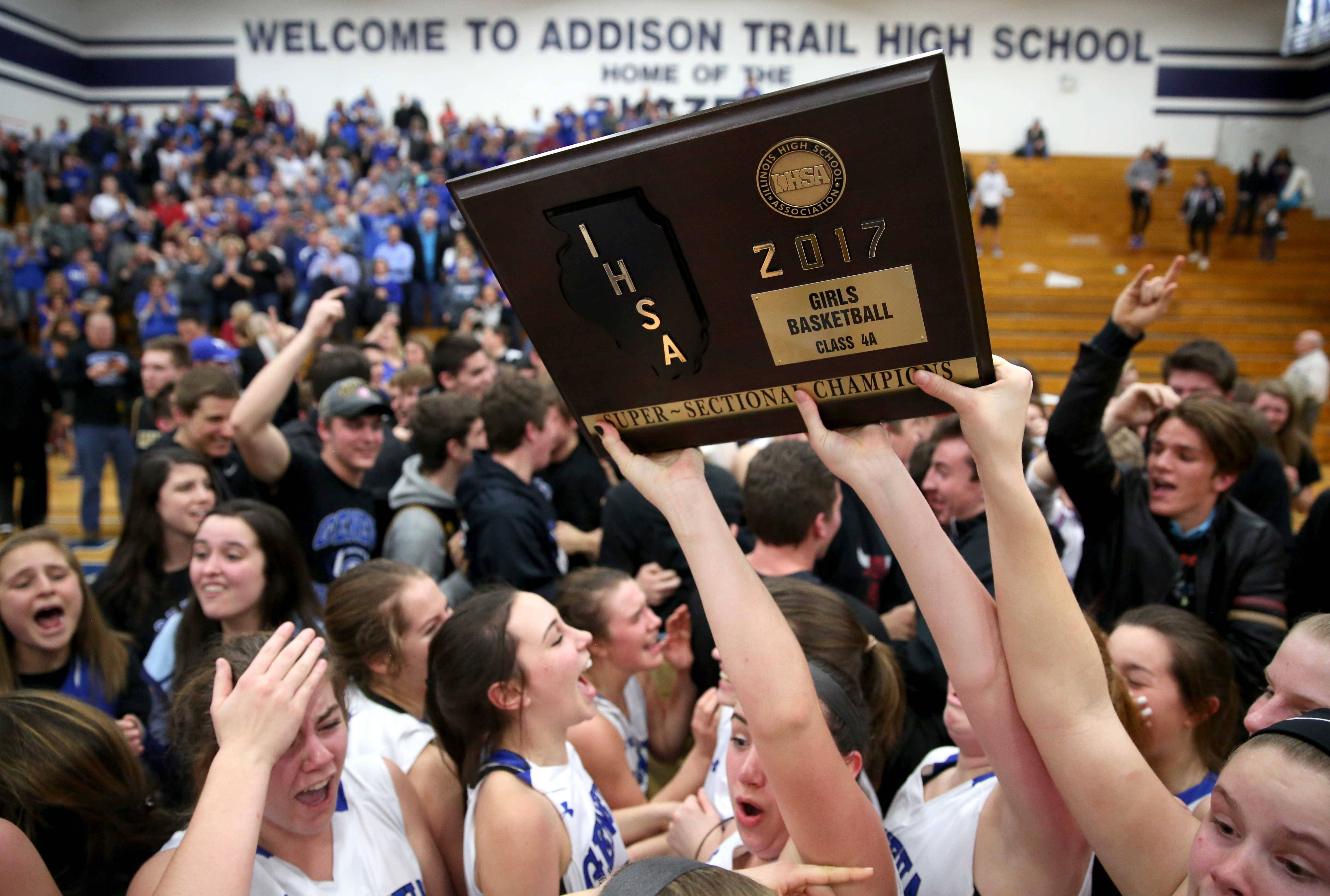 The Vikings of Geneva hoist their hardware after a win over Maine West during girls basketball supersectional action at Addison Trail High School Monday night.