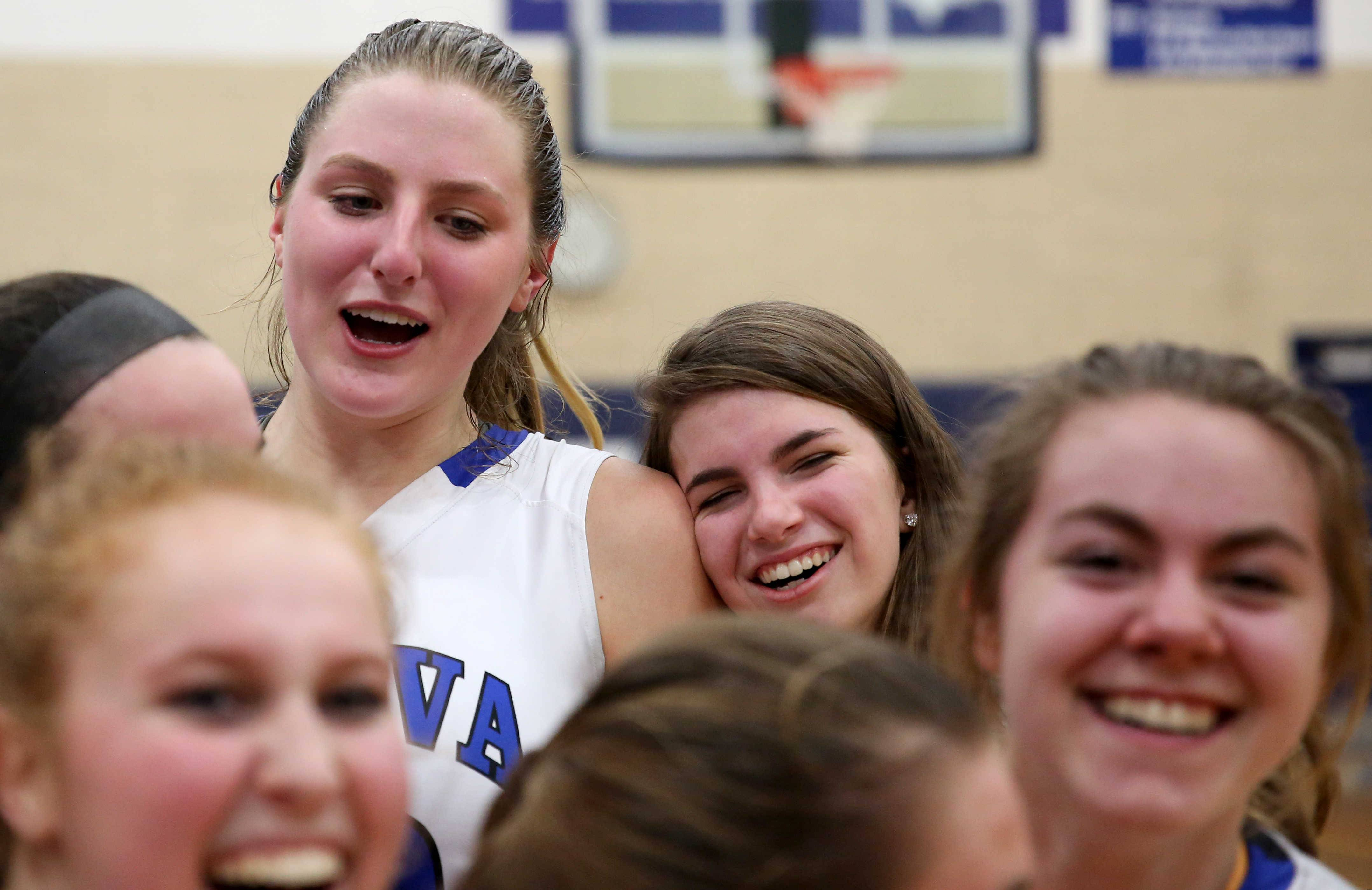 Grace Loberg and the Lady Vikings of Geneva are all smiles after their win over Maine West during girls basketball supersectional action at Addison Trail High School Monday night.