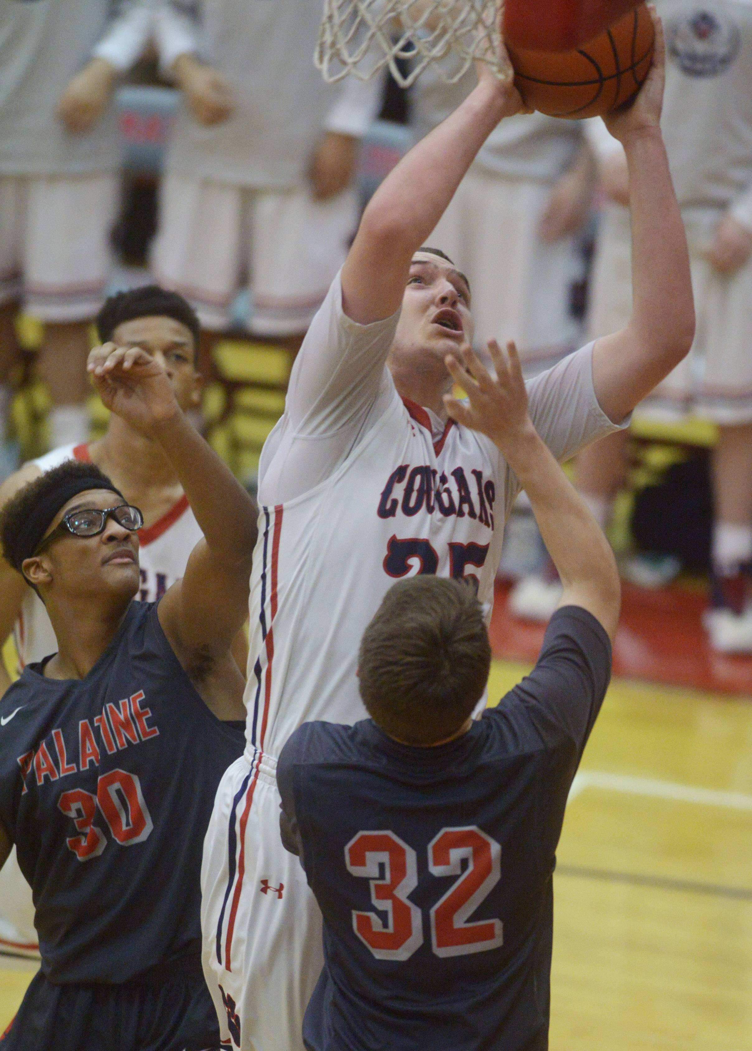 Conant's Ryan Davis makes a basket down low as Palatine's Cortez Hogans, left, and Scott Elter defend during Class 4A regional semifinal play at Palatine on Tuesday.