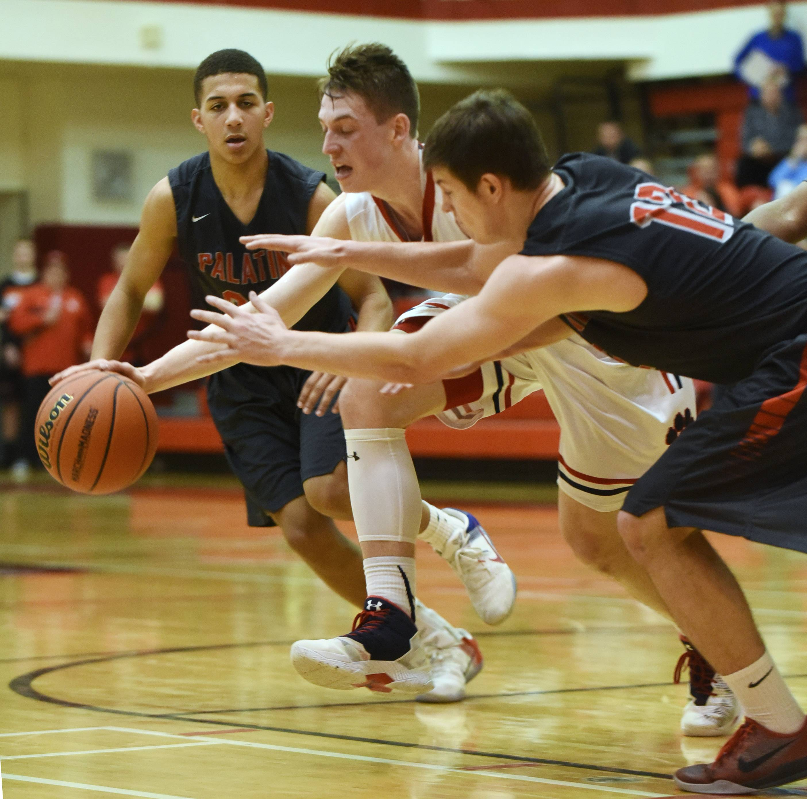 Conant's Jimmy Sotos, right, tries to maintains possession of the ball while making a move between Palatine's Lamon Berry, left, and Johnny O'Shea during the Class 4A regional semifinal at Palatine on Tuesday.