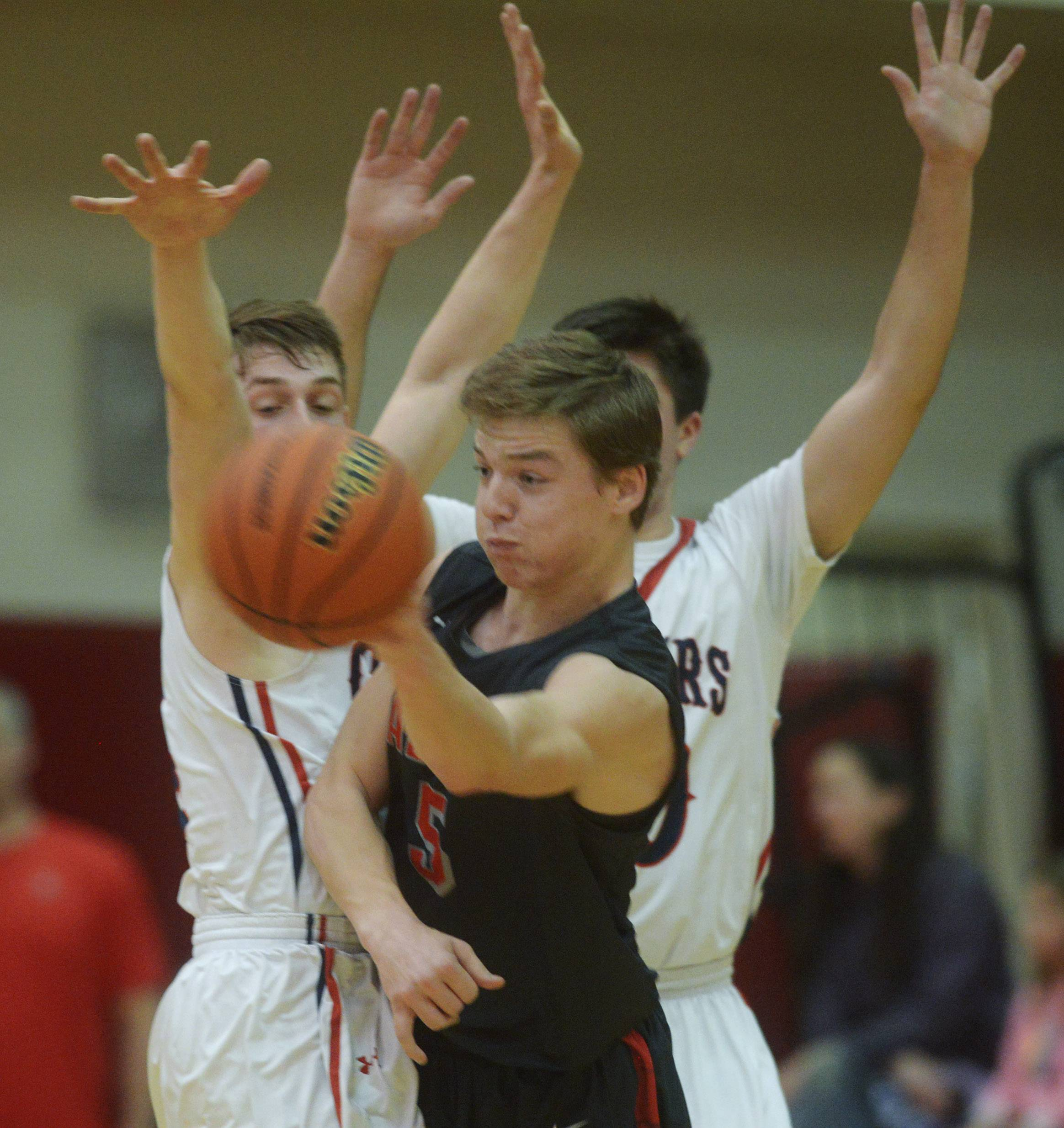 Palatine's Jake Moertl passes while being pressured by Conant's Jimmy Sotos, left, and Ben Schols during the Class 4A regional semifinal at Palatine on Tuesday.
