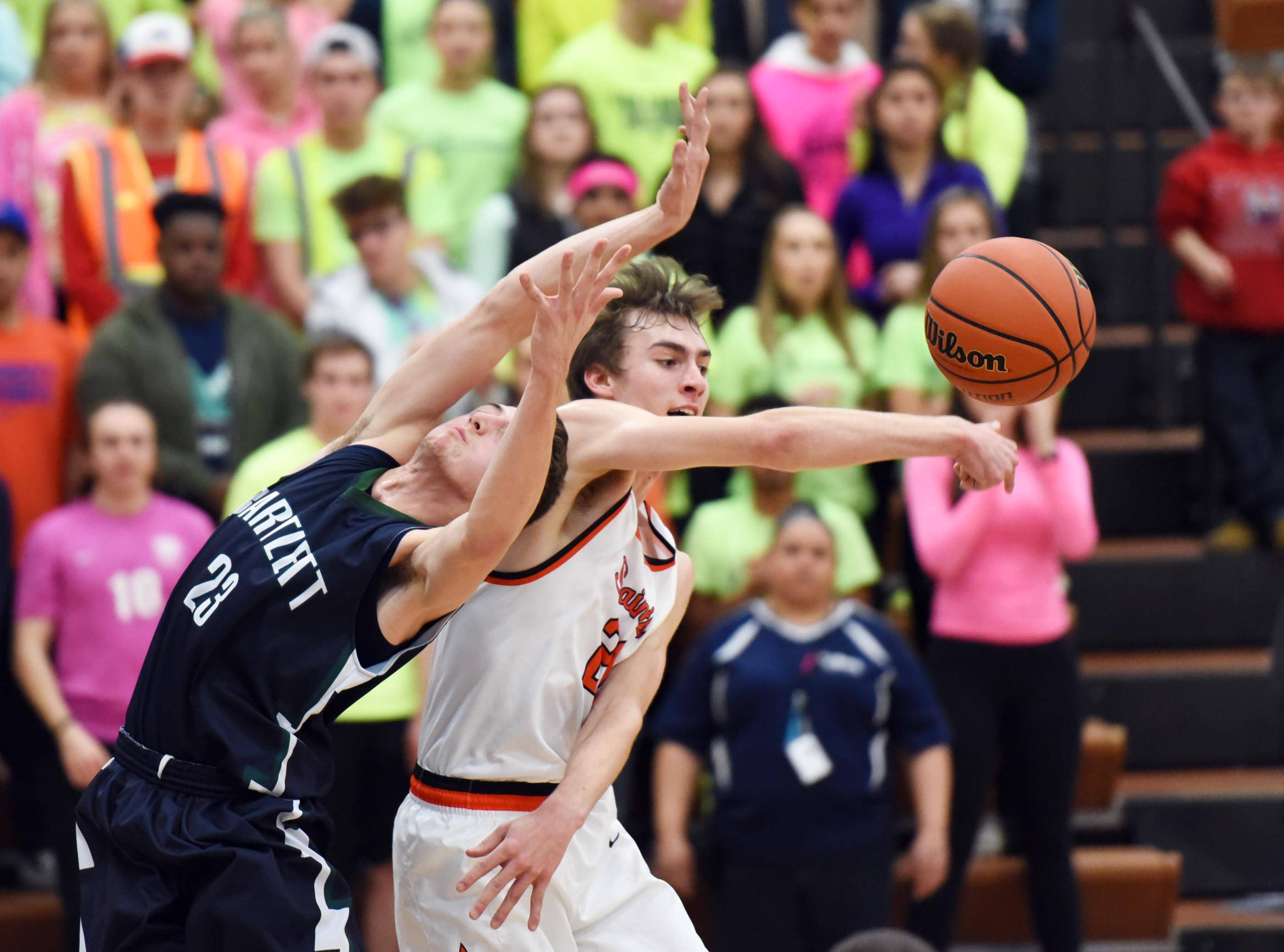 St. Charles East's Wade Kyle swats the ball away from  Bartlett's Ben Tompson Wednesday at the boys basketball regional tournament game in Elgin.