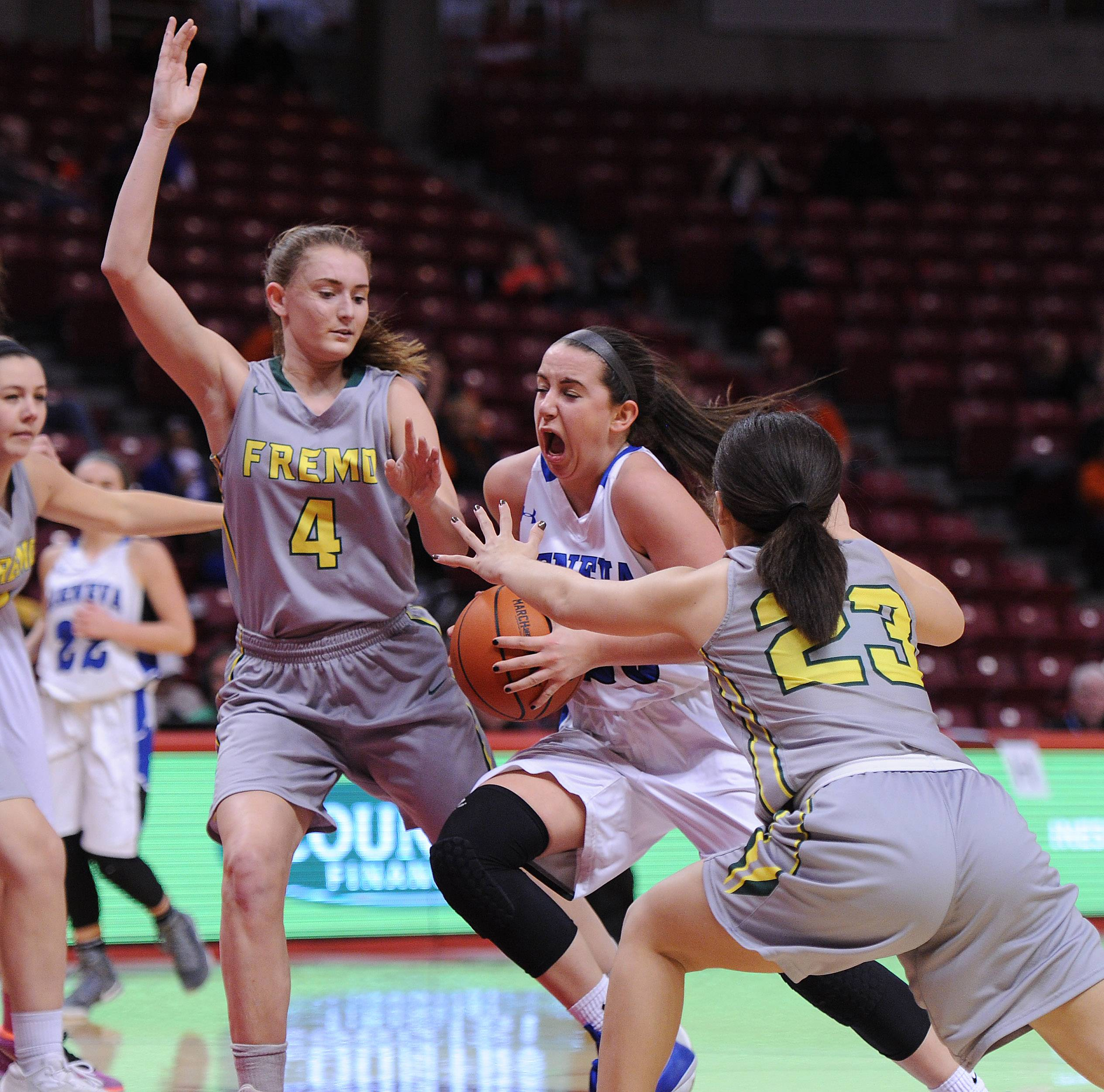 Geneva's Margaret Whitley powers her way through Fremd defenders Missy Adrian and Hayley Williams in the first half of the Class 4A girls basketball state semifinals in Normal on Friday.