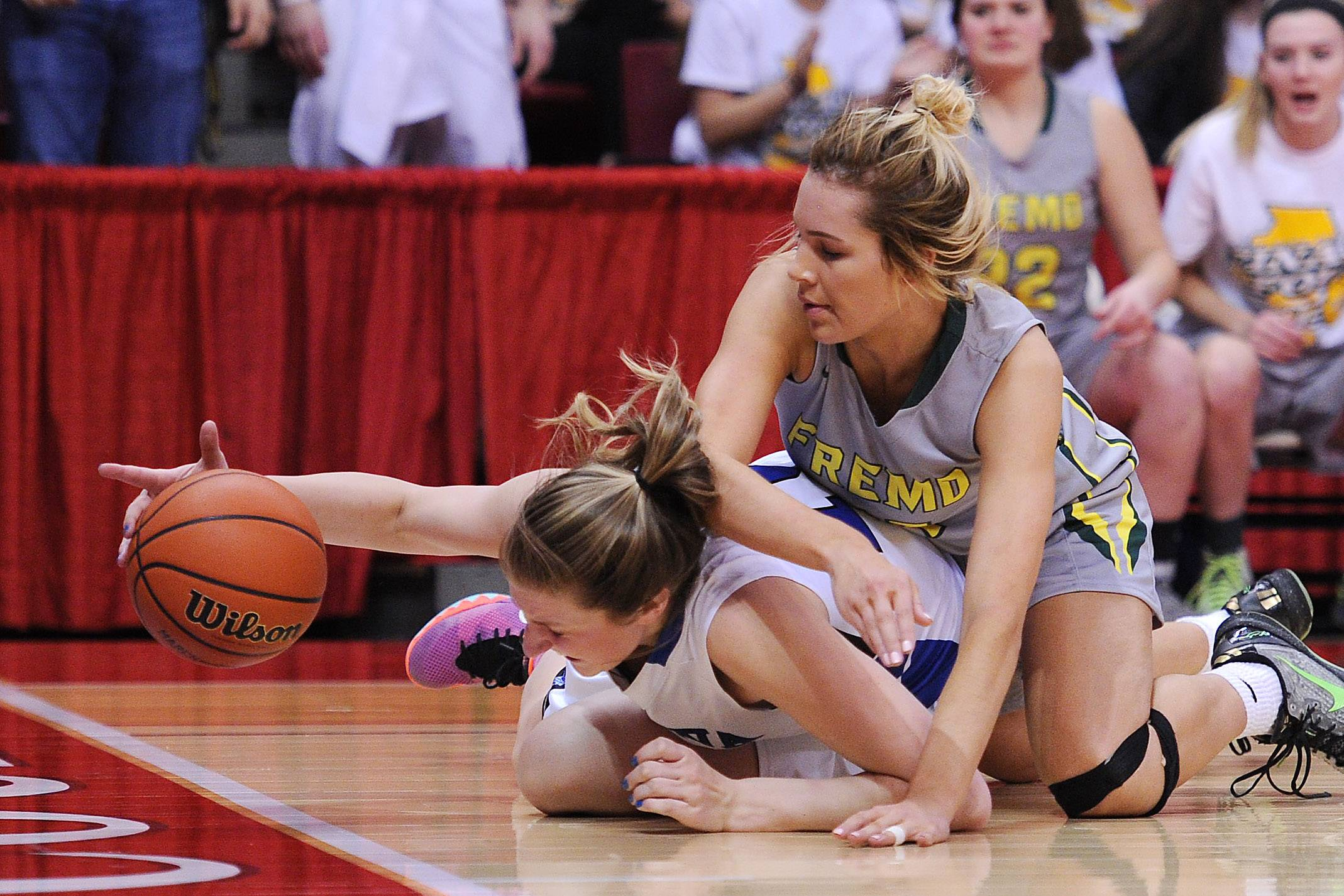 Geneva's Grace Loberg reaches for a loose ball as Fremd's Grace Tworek applies pressure in the first half of the Class 4A girls basketball state semifinals in Normal on Friday.