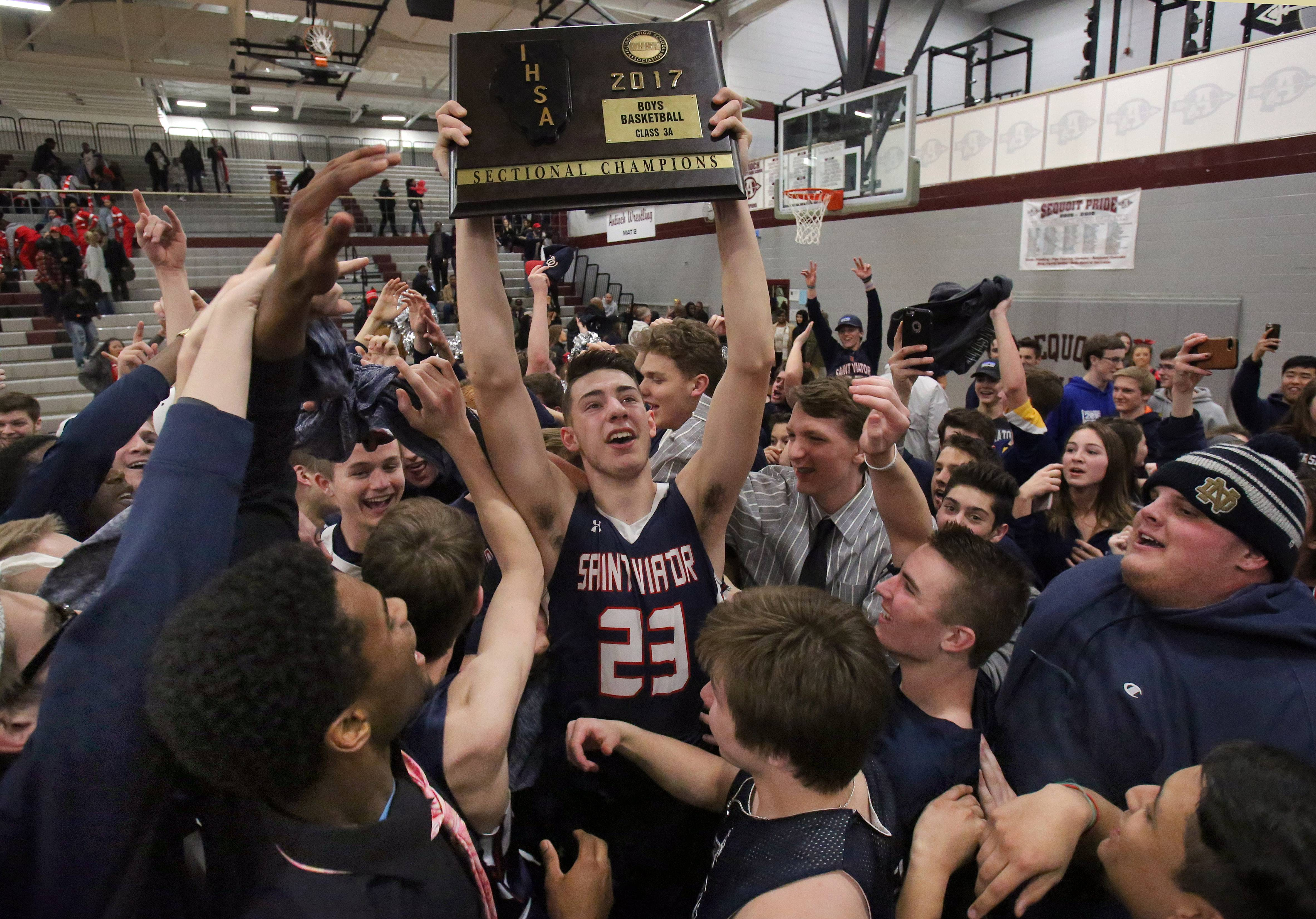 St. Viator's Tom Majerus hoists the sectional trophy after the Lions' overtime win against North Chicago in the Class 3A sectional final at Antioch on Friday.
