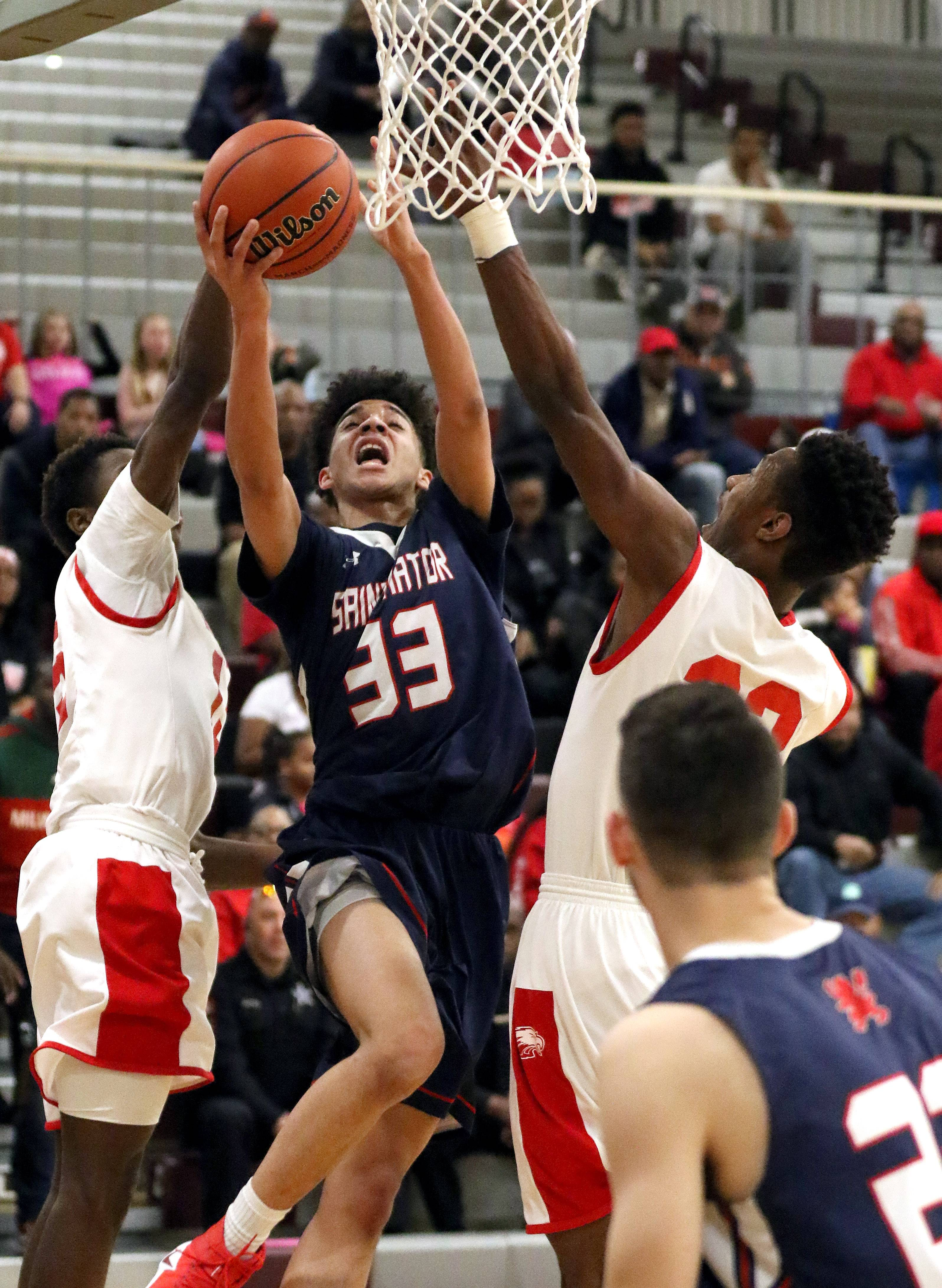 St. Viator's Jeremiah Hernandez (33) drives on North Chicago's Pierce Coleman, left, and Terrell Grier in the Class 3A sectional final at Antioch on Friday.