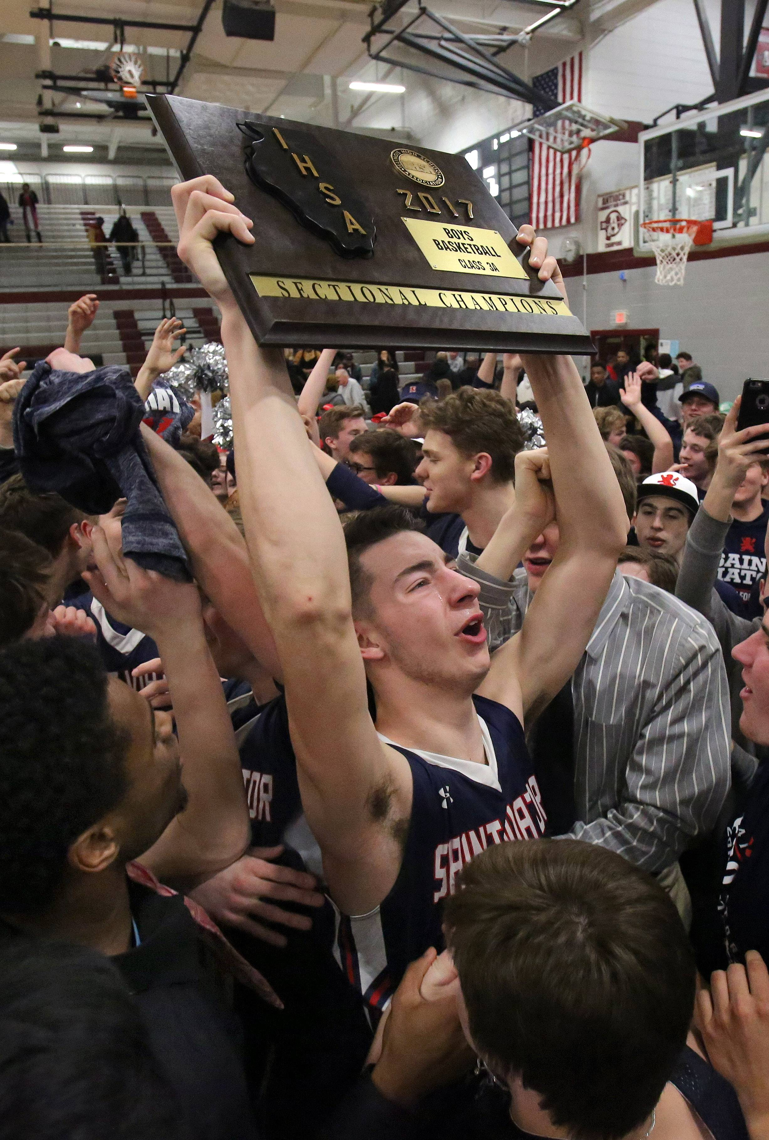 St. Viator's Tom Majerus lifts the sectional trophy after the Lions' overtime win over North Chicago in the Class 3A sectional final at Antioch on Friday.