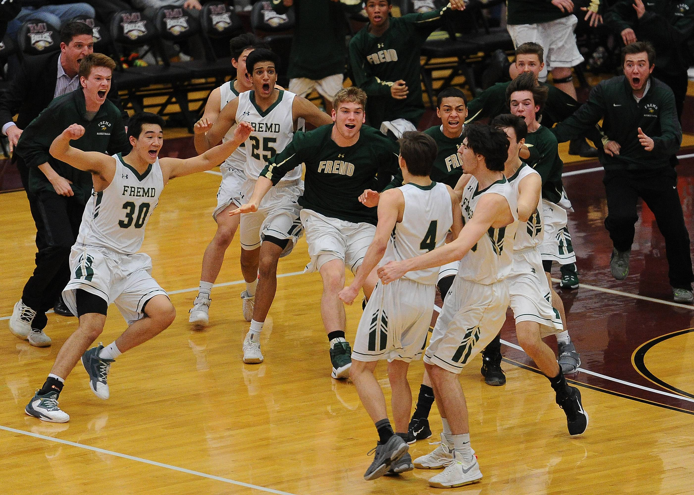 Kyle Sliwa's teammates rush the floor after his 3-pointer were the decisive points in Fremd's 43-42 victory Conant in Class 4A sectional final play Friday at Robert Morris University.