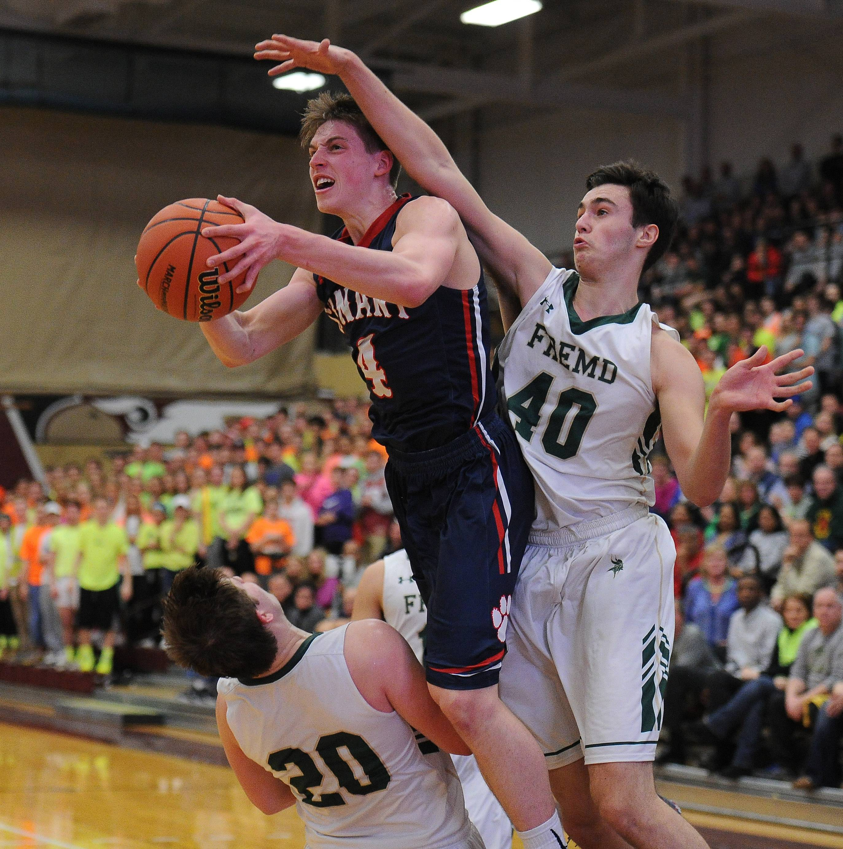 Fremd's Mark Kating and teammate Luke Schoffstall defend against Conant senior guard Jimmy Sotos on a drive to the basket in Class 4A sectional championship play at Robert Morris University on Friday.