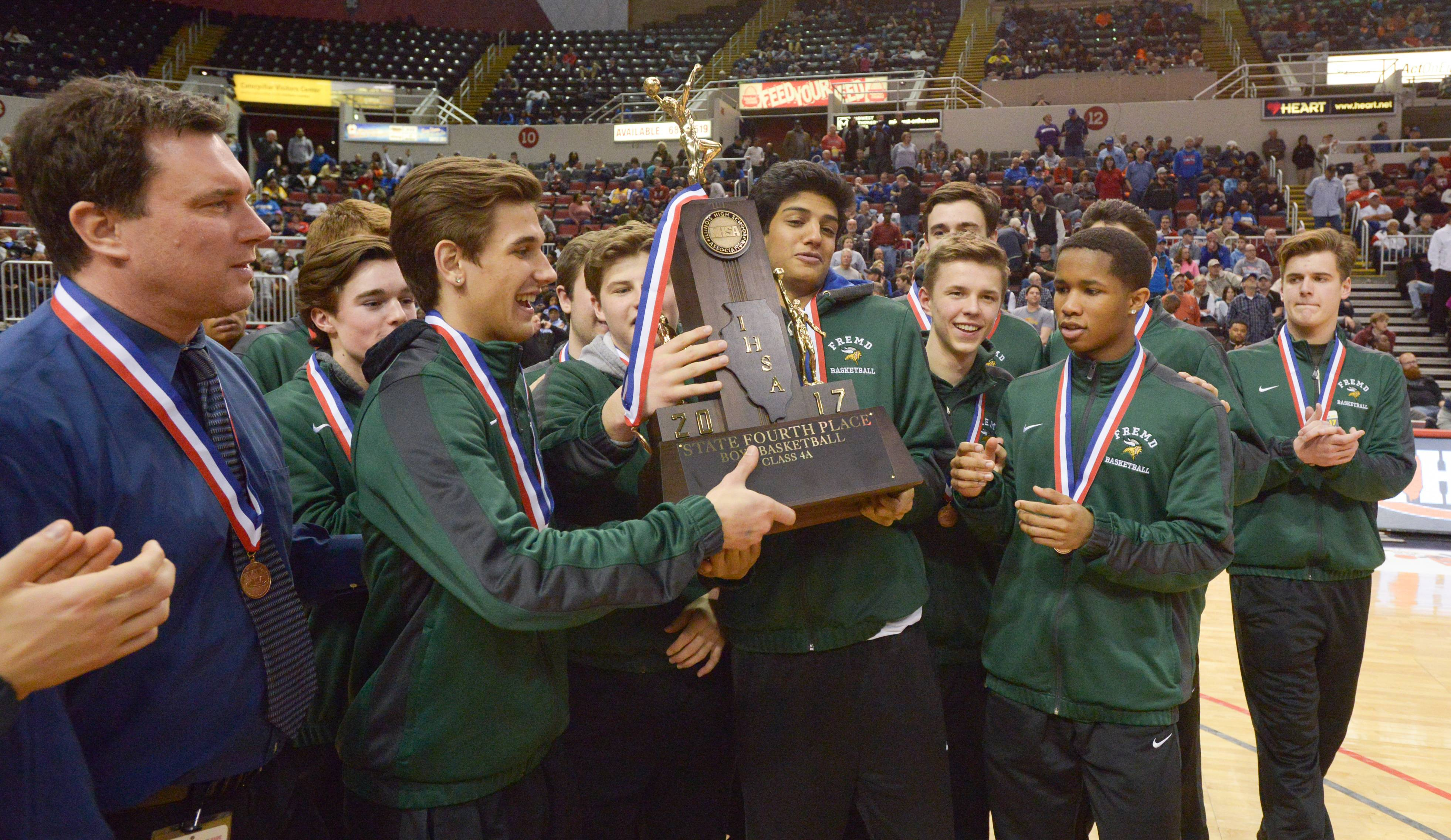 Fremd's boys basketball team including coach Bob Widlowski, left, gladly accepts the state's fourth-place trophy after falling to Bolingbrook 70-66 in Class 4A third-place game Saturday in Peoria.