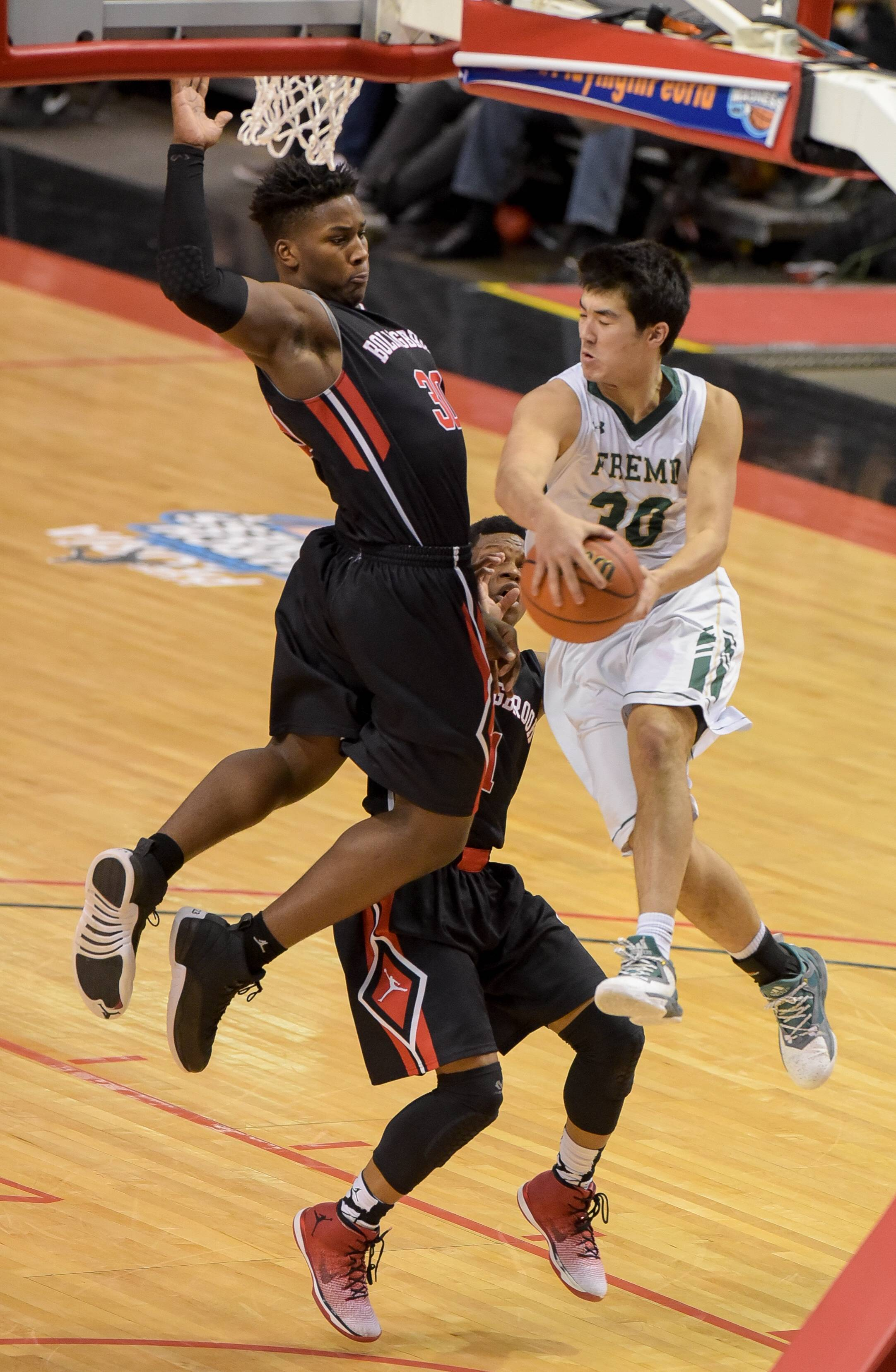 Fremd's Ryan Martin fakes a shot and passes around Bolingbrook's Malik Binns during the Class 4A third-place game on Saturday in Peoria.