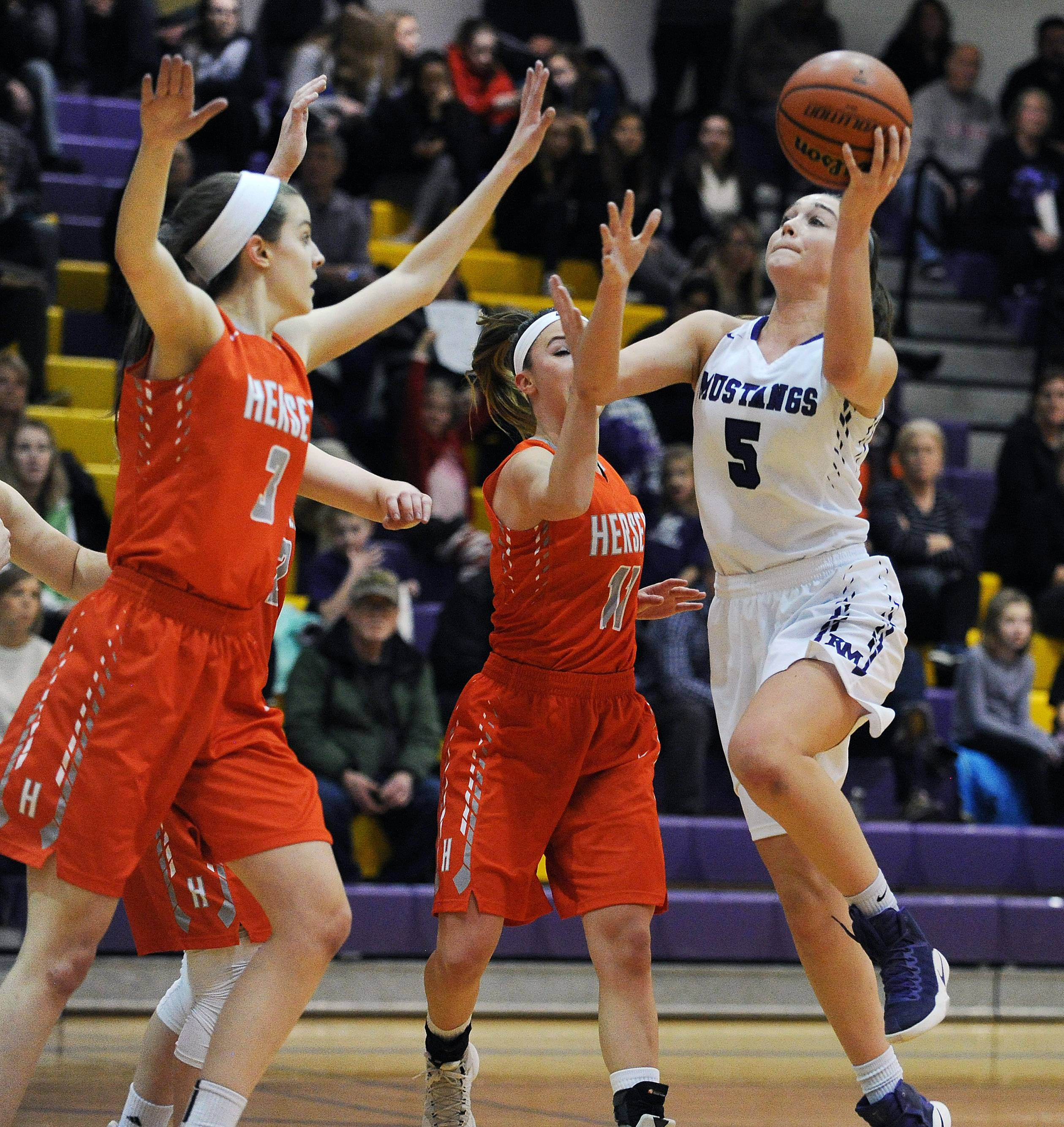 Rolling Meadows' Kyra Spiwak, here driving to basket against Hersey, has committed to a collegiate basketball future at Providence.