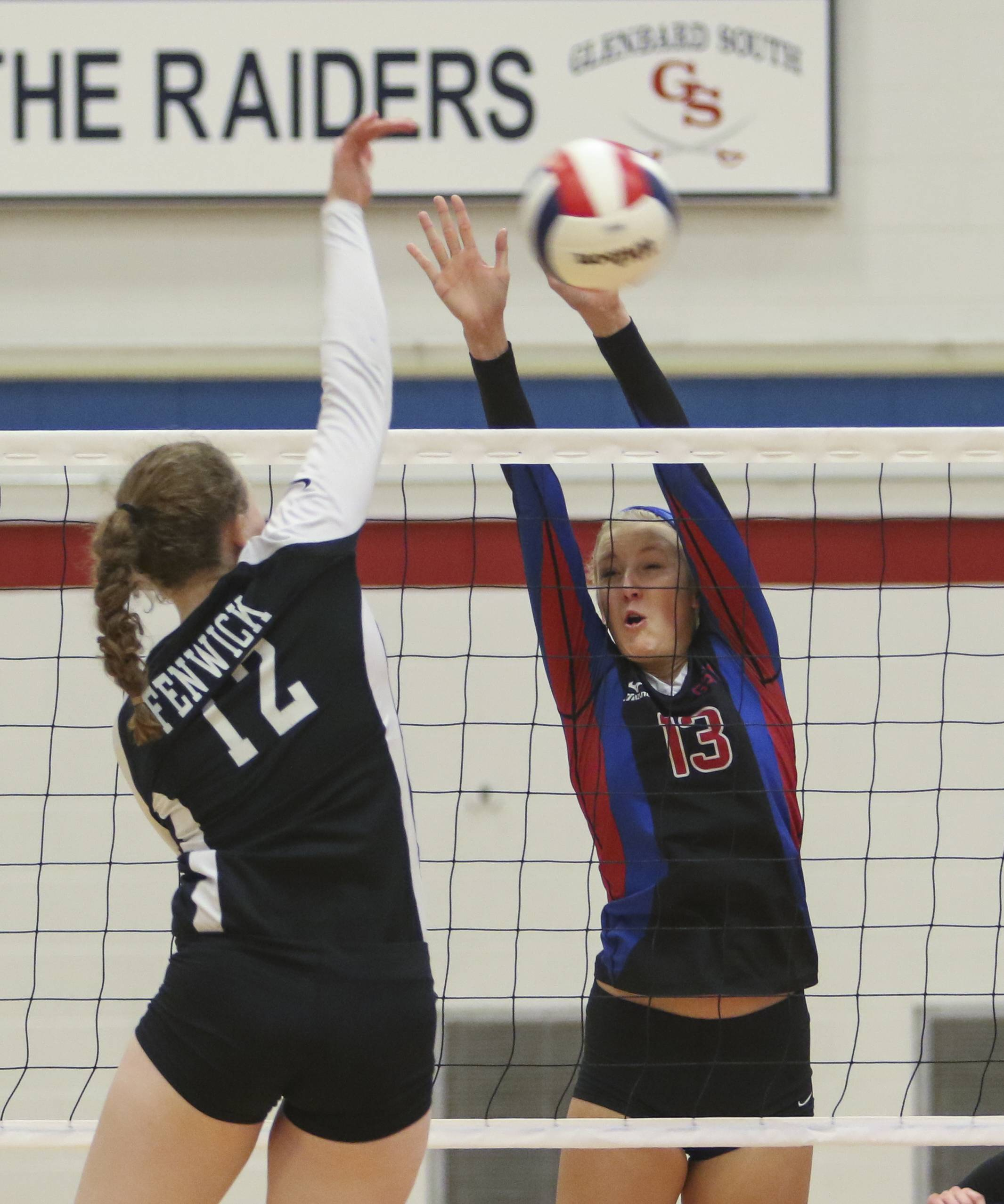 Glenbard South's Bella Bauman blocks the ball from Margaret Planek of Fenwick  during Class 3A Glenbard South girls volleyball sectional semifinals on Tuesday in Glen Ellyn.