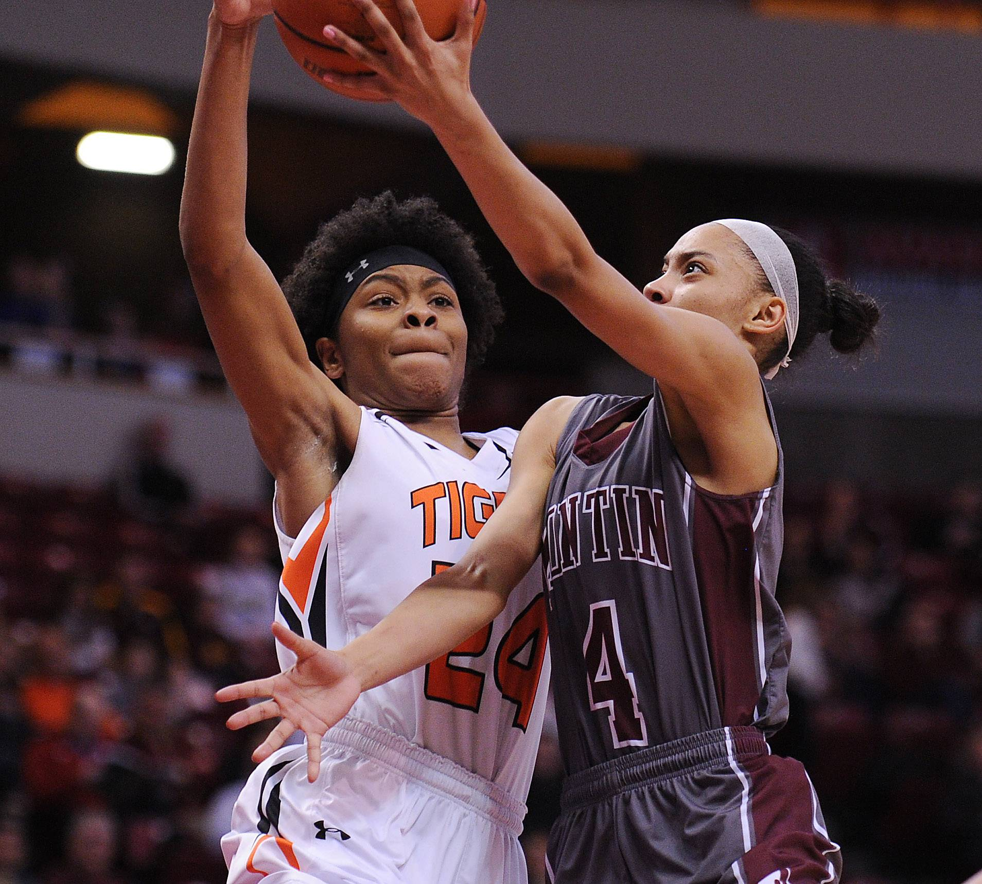 Montini's Ilysse Pitts battles Edwardsville's Myriah Haywood as she moves to the basket in the first half of the girls basketball Class 4A semifinal in Normal, Illinois on Friday.