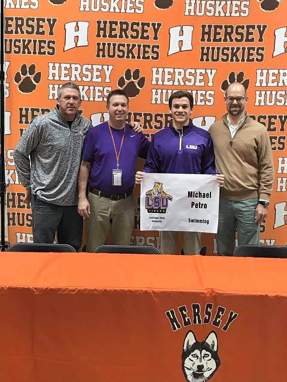 From left, Hersey athletic director Steve Messer, coach Dick Mortensen, Michael Petro and assistant coach Jeff Baker gather to announced Petro's signing with the Louisiana State swimming program.