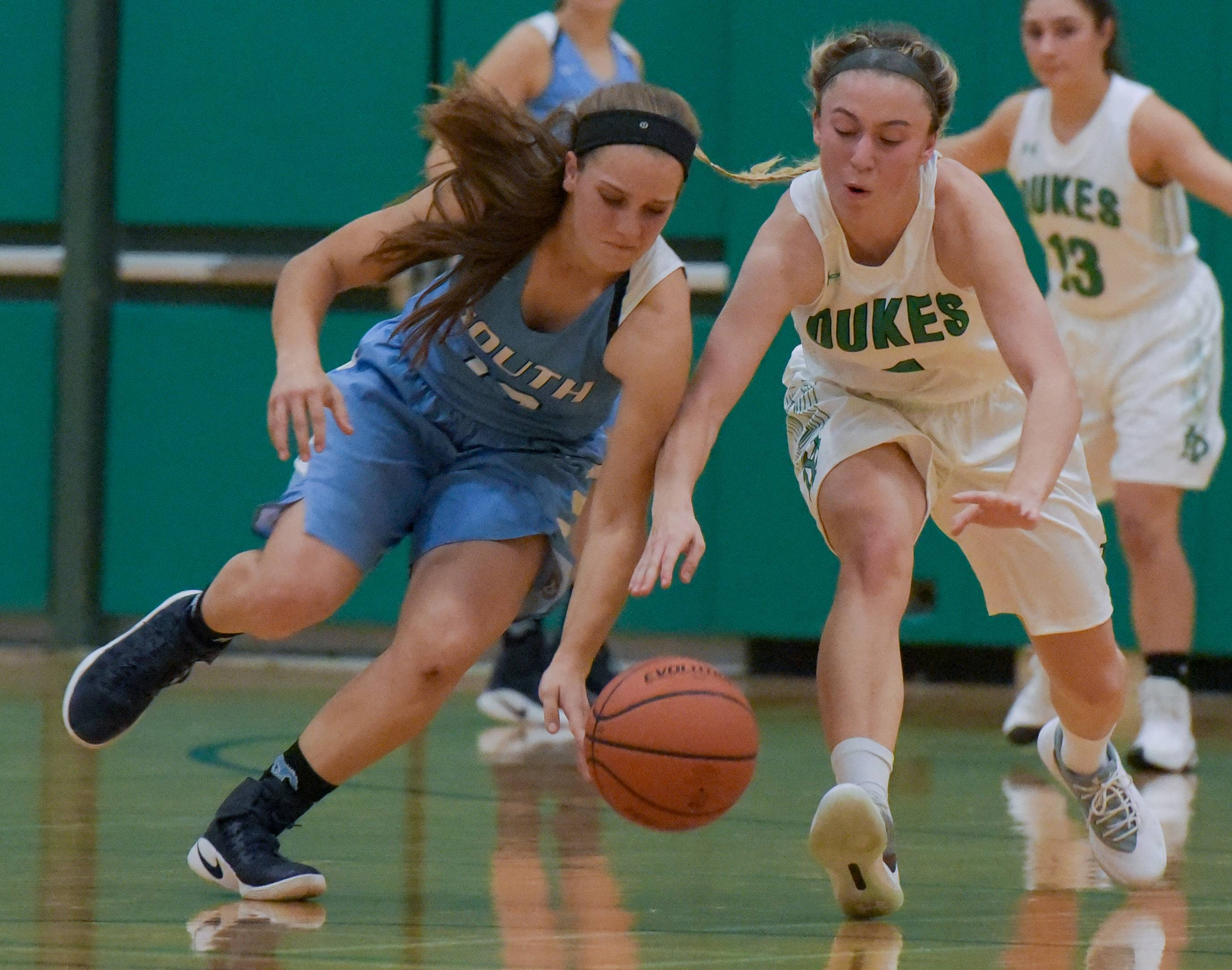 Downers Grove South's Maggie Greco (13) and York's Madison Park (1) scramble for a loose ball during the York High School Thanksgiving girls basketball tournament on November 14, 2017.