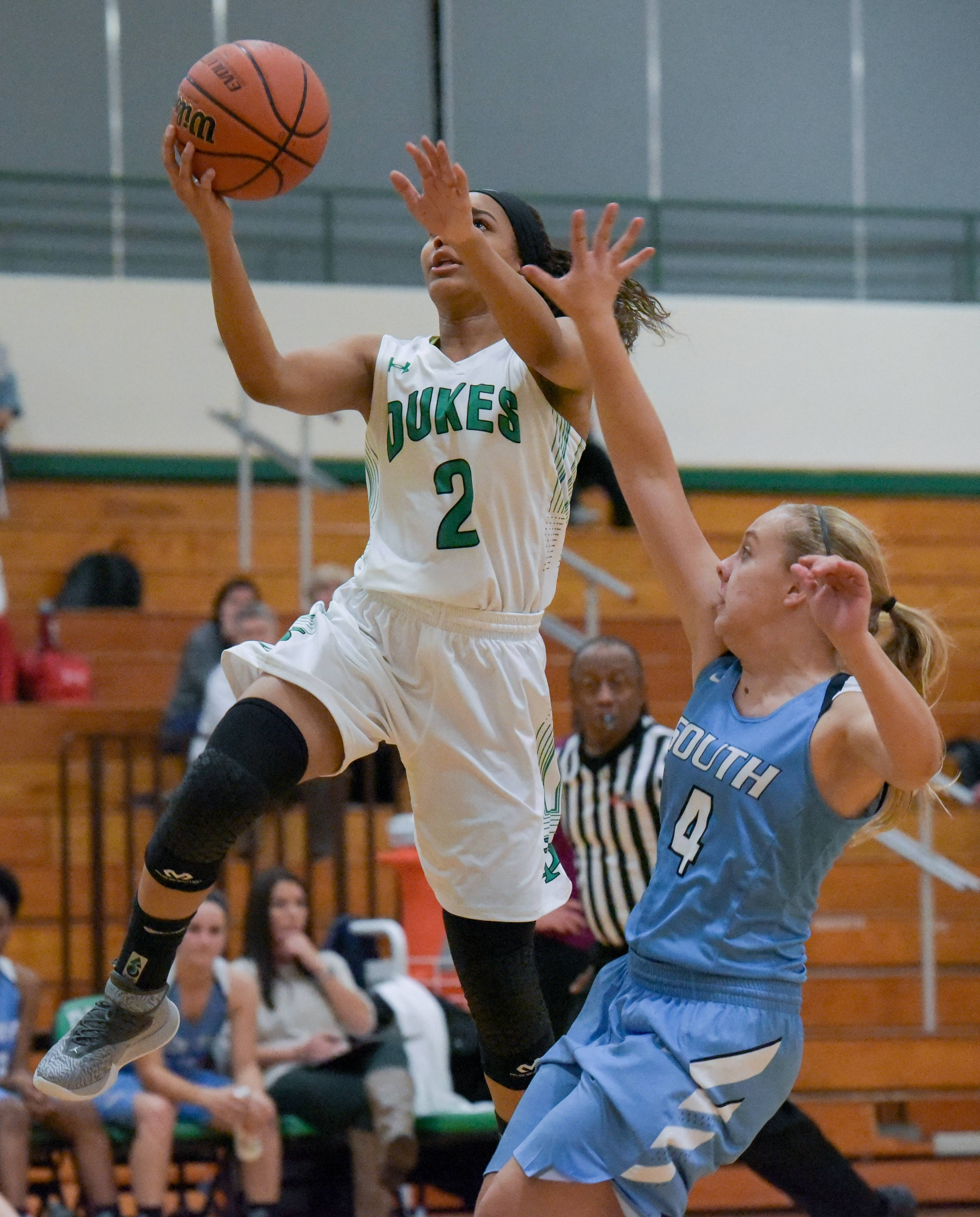 York's Kiah Rufus (2) lays up for a shot over Downers Grove South's Angel Biondo (4) during the York High School Thanksgiving girls basketball tournament on November 14, 2017.