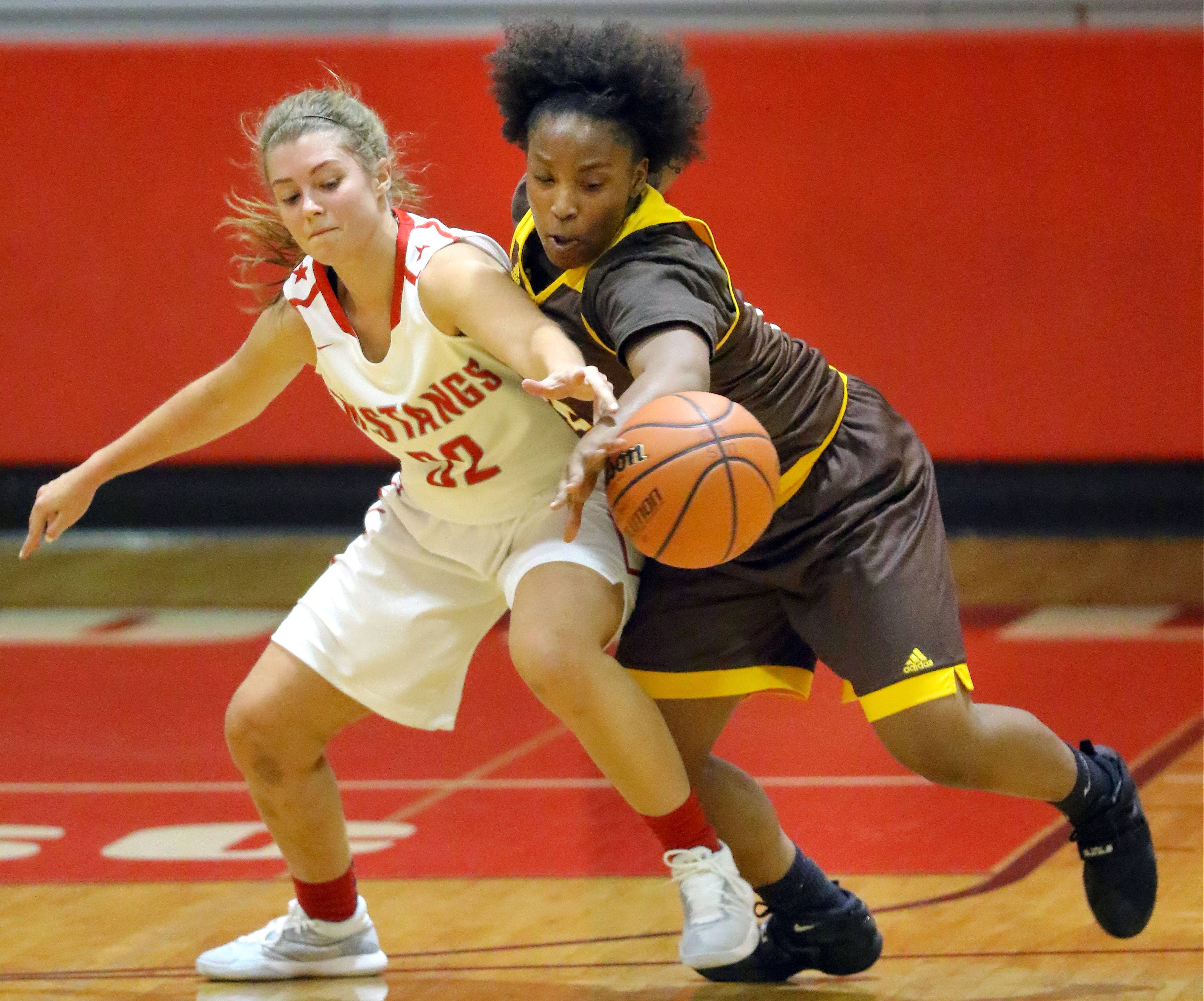 Mundelein's Kelsey Austwick, left, has the ball stolen by Carmel's Taryn Dwyer.