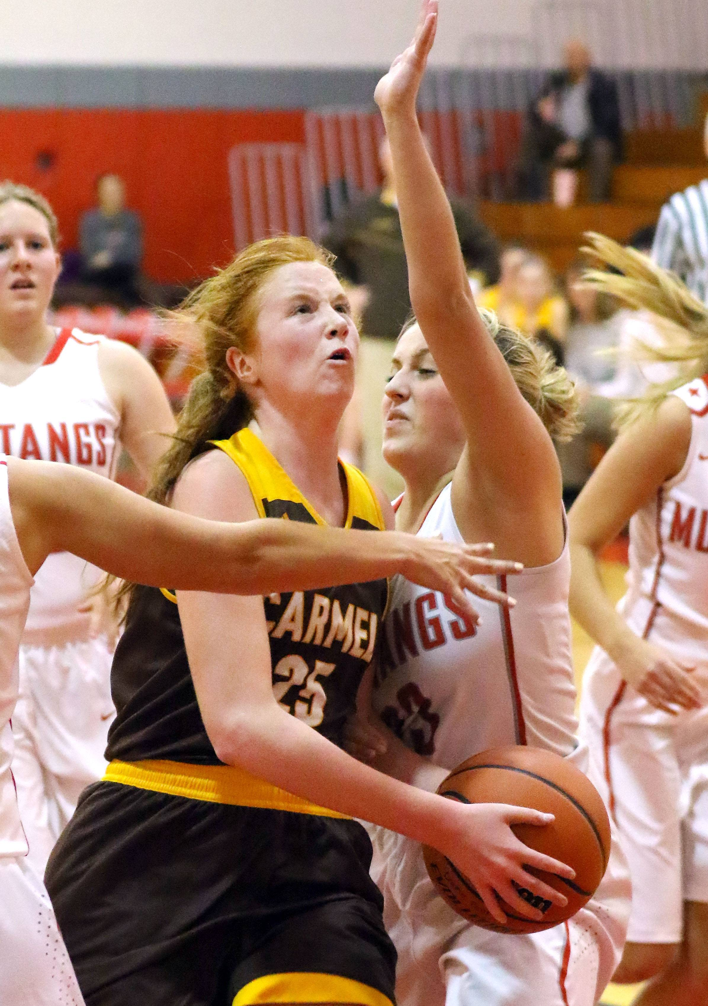 Carmel's Brigit Barr, left, drives on Mundelein's Madison Parola on Tuesday at Mundelein.