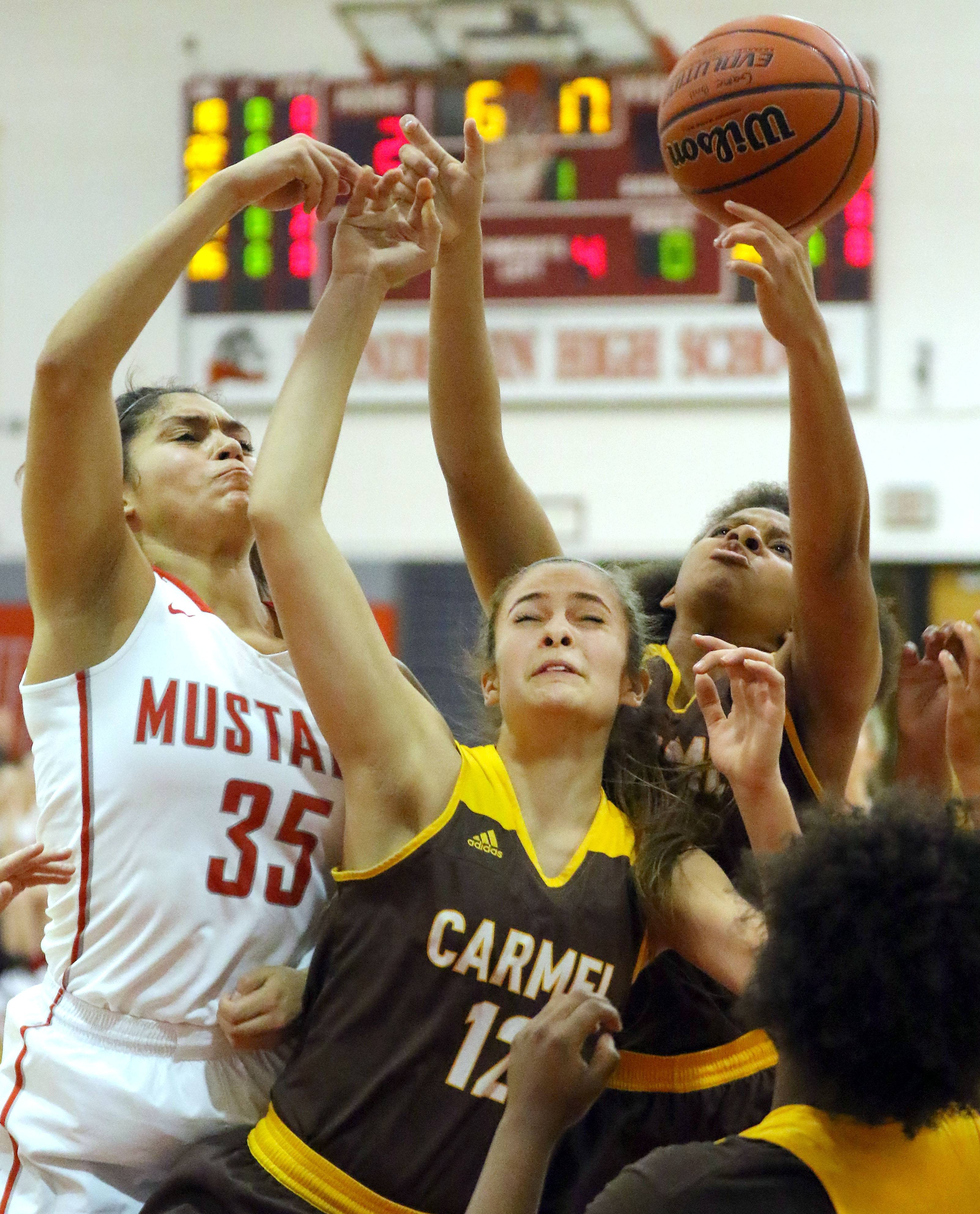 Mundelein's Ellie Maldonado (35) battles for a rebound with Carmel's Kaytlyn Matz and Shai Horton on Tuesday.
