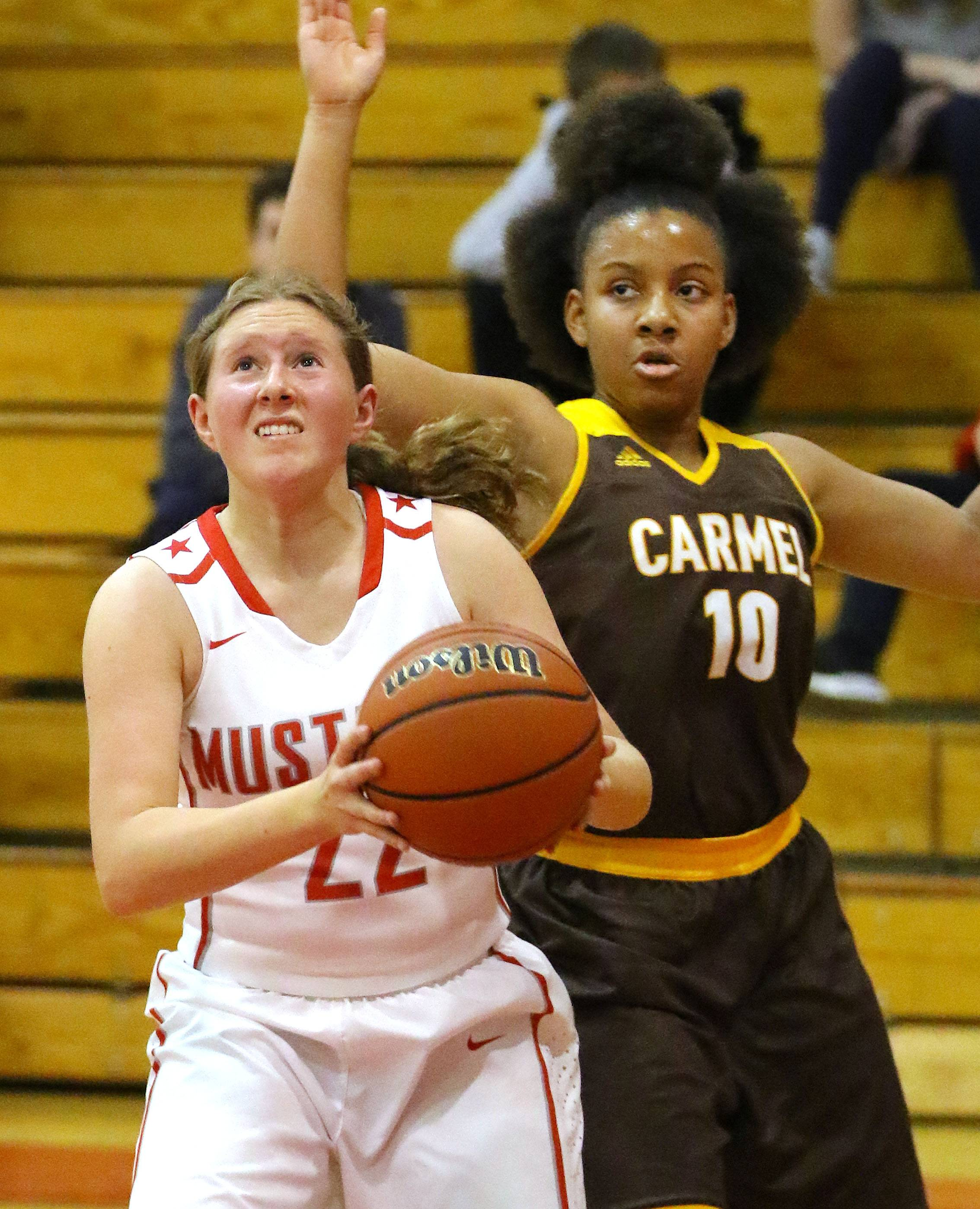 Mundelein's Hannah Buscher, left, drives past Carmel's Shai Horton on Tuesday at Mundelein.
