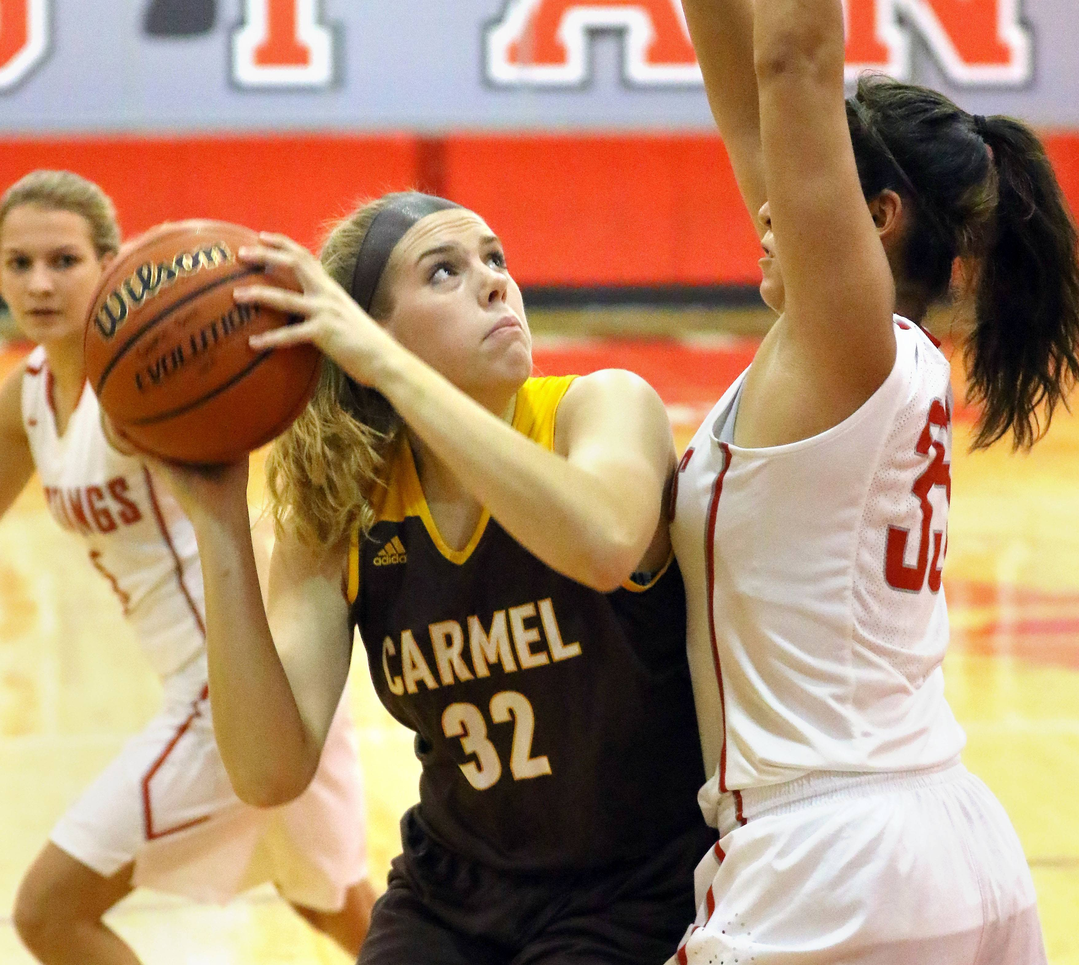 Carmel's Maddie Motzel, left, looks to shoot with Mundelein's Ellie Maldanado defending on Tuesday at Mundelein.