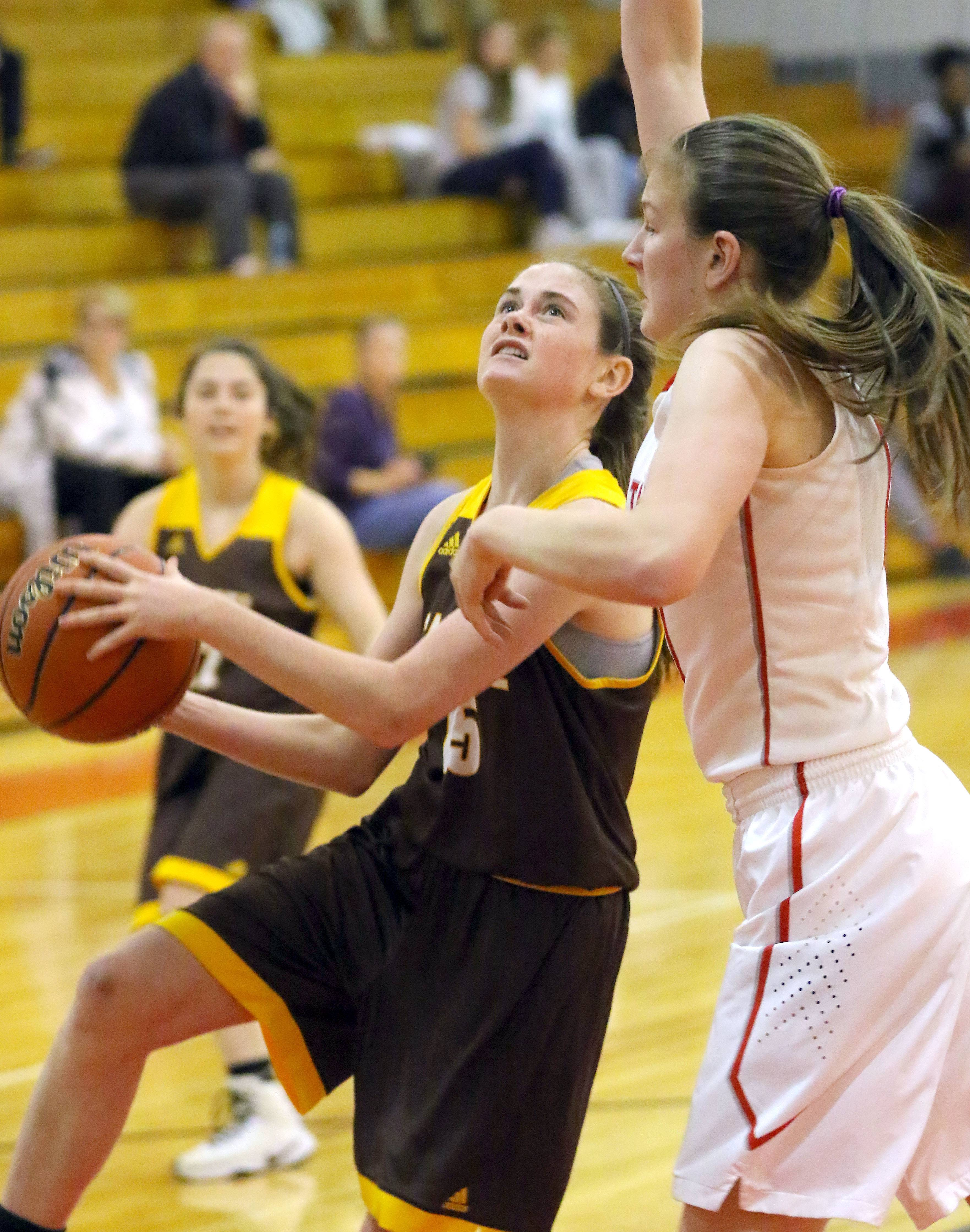 Carmel's Caitlin Teehan, left, drives on Mundelein's Morgan Frank on Tuesday at Mundelein.