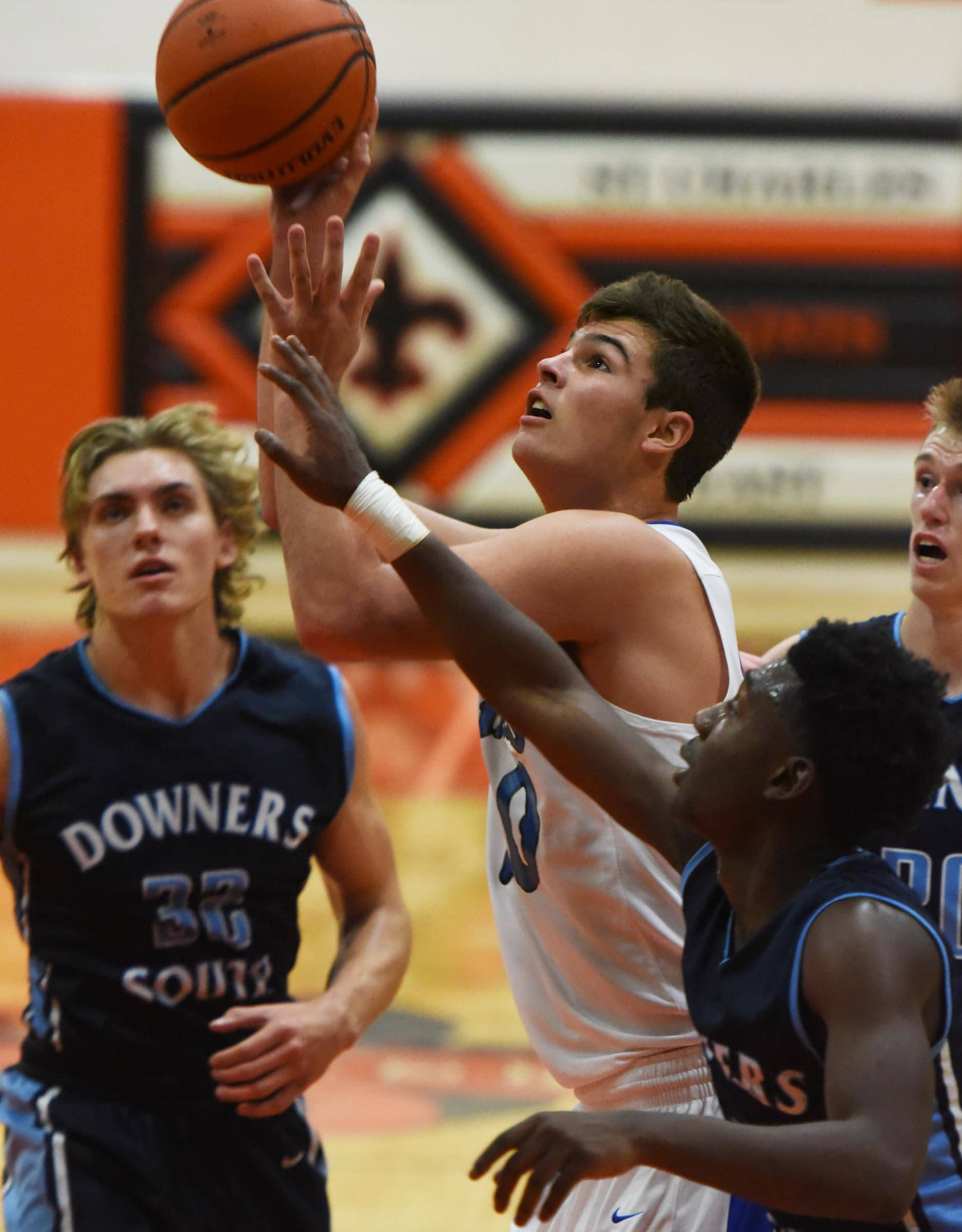 St. Charles North's Kyle King shoots while surrounded by Downers Grove South players last season.