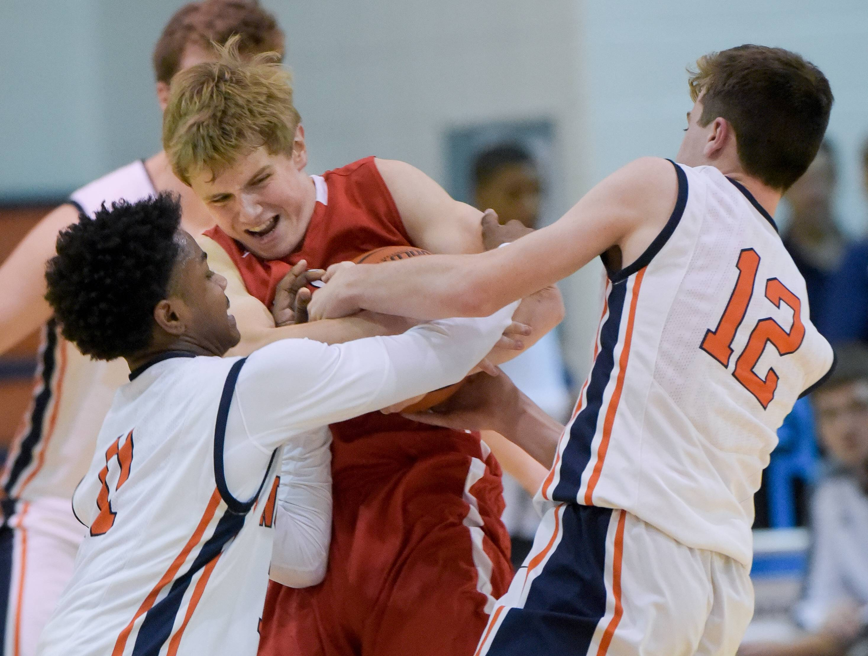 Naperville North's Jared McIntyre (11) and Jack Hill (12) struggle with Hinsdale Central's Trevor Hamilton (13) for control of the ball during boys varsity basketball on November 20, 2017.