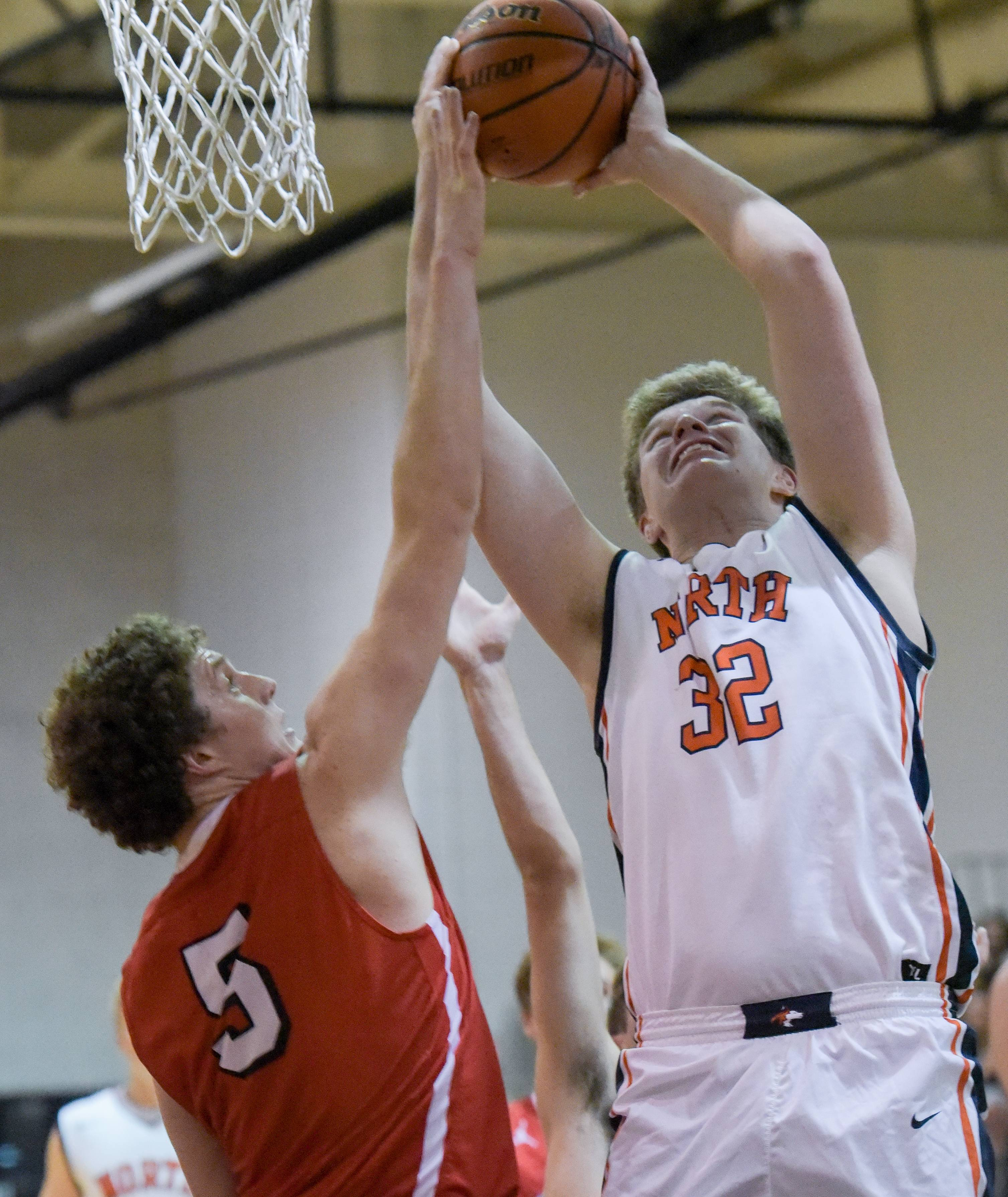 Hinsdale Central's Mac Quast (5) attempts to block a shot by Naperville North's Chris Johnson (32) during boys varsity basketball on November 20, 2017.