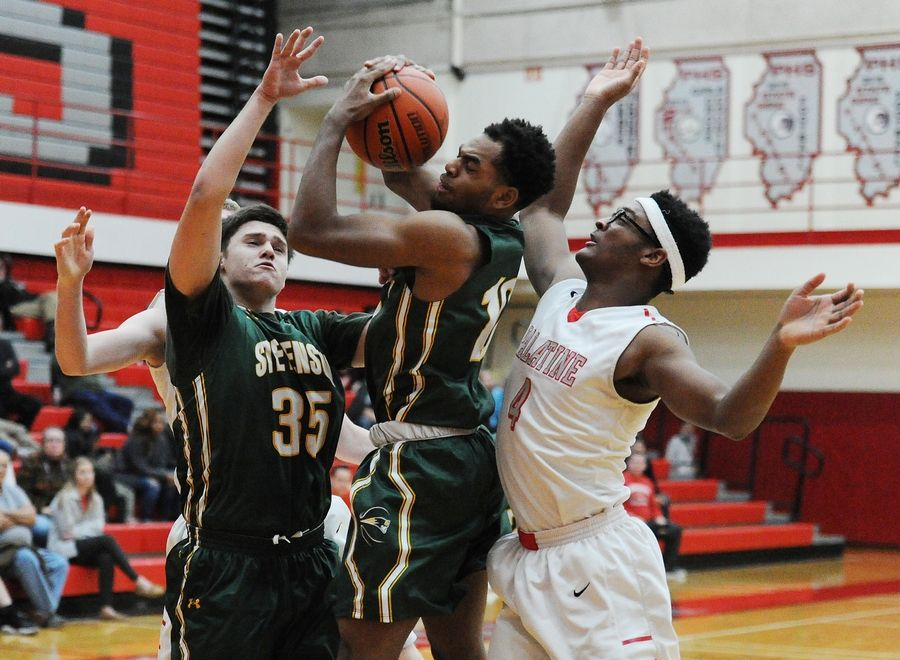 Stevenson's Kyree Lewis battles for a rebound with Palatine's Cortez Hogans in tournament play Friday at Palatine.