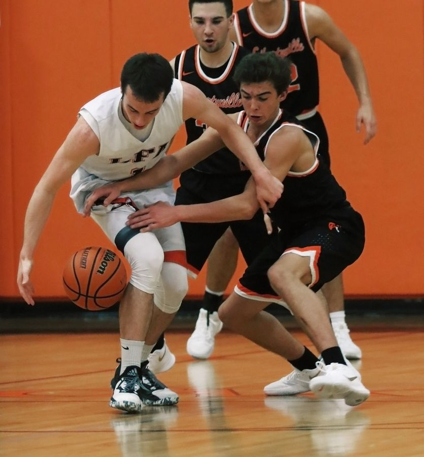Lake Forest Academy guard Benjamin Canady, left, battles for the ball against Libertyville guard Brian Wilterdink in Lake Forest on Thursday.