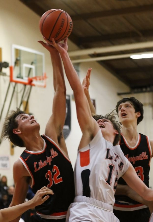 Libertyville forward Travis Clark, left, battles Lake Forest Academy forward Joshua Arrowood for a rebound on Thursday in Lake Forest.
