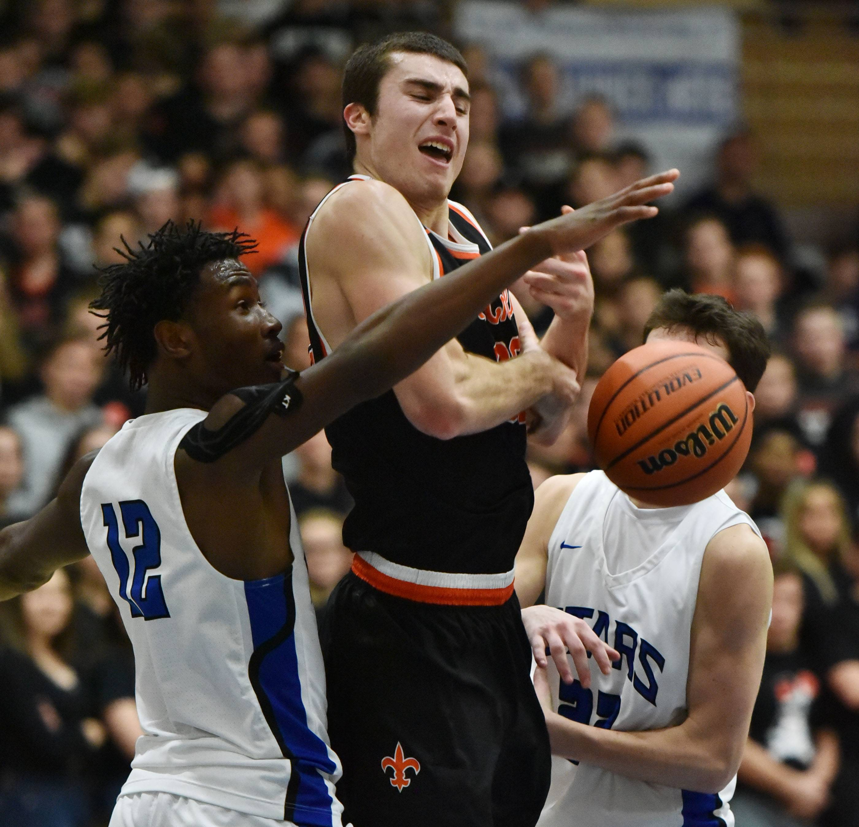 St. Charles East's Justin Hardy loses the ball under the defense of St. Charles North's Tyler Nubin and Cade Callaghan Friday at North High School.