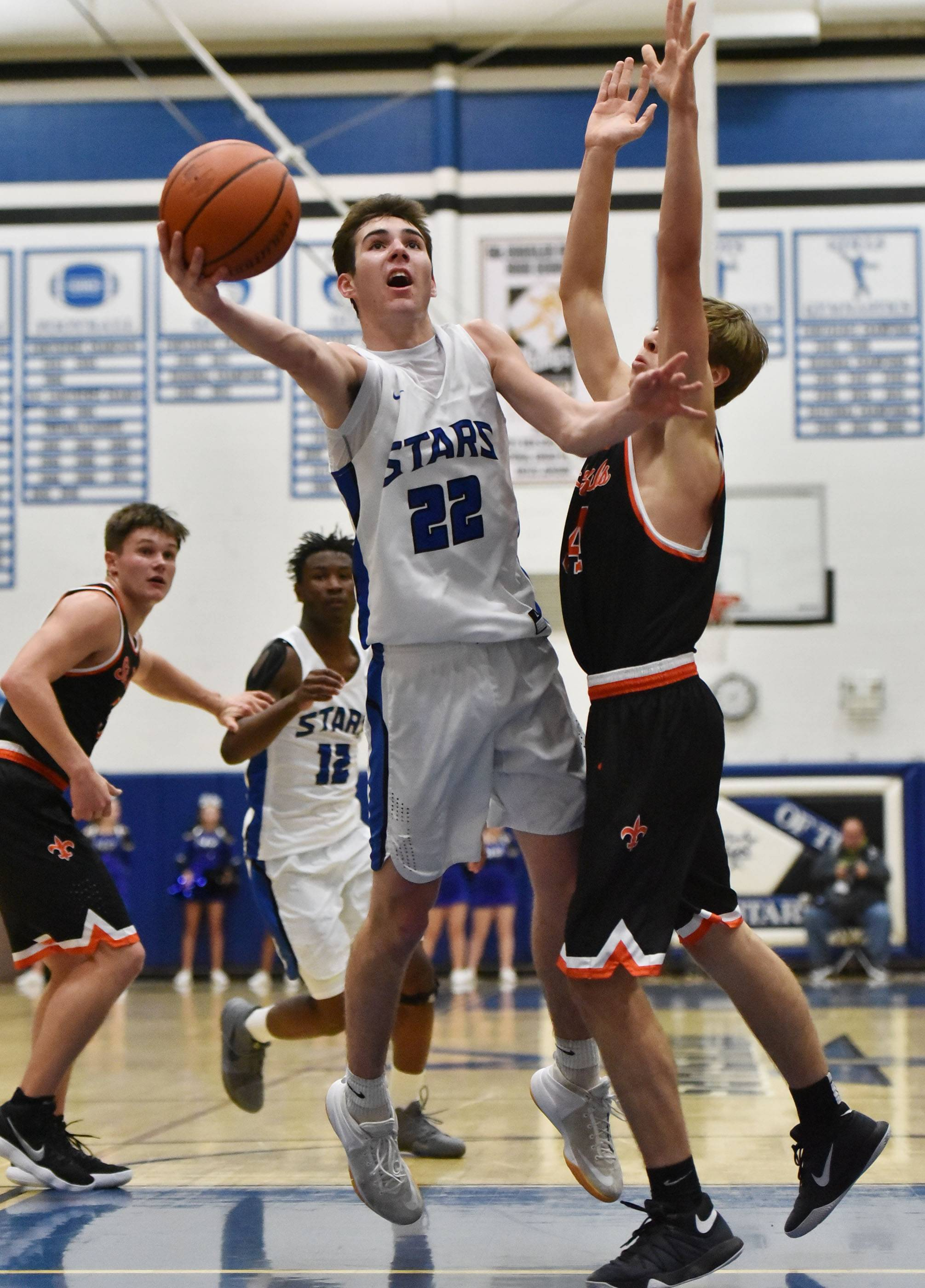 St. Charles North's Cade Callaghan scoops a shot against St. Charles East's Aidan Sullivan Friday.
