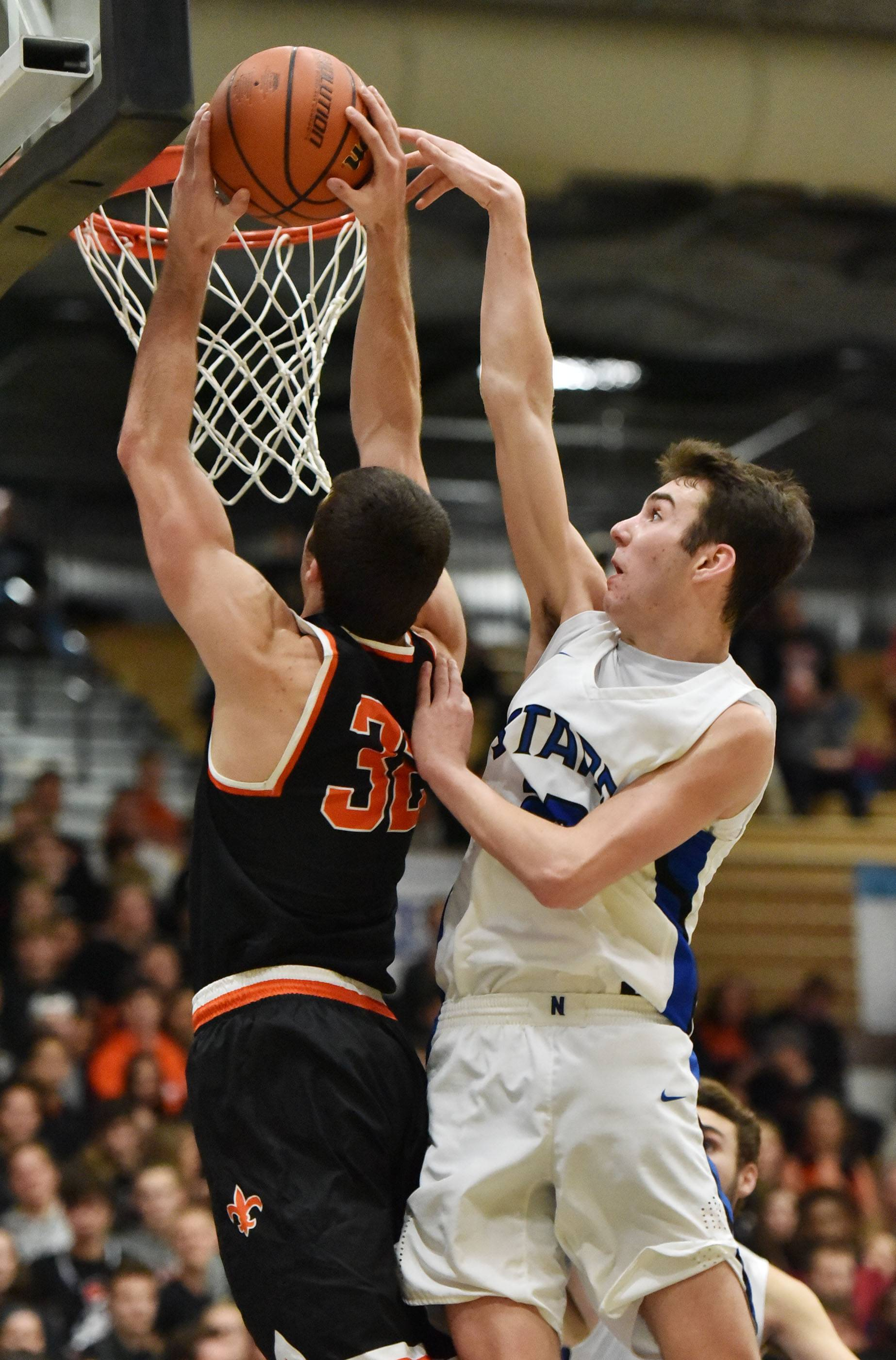 St. Charles North's Cade Callaghan fouls St. Charles East's Justin Hardy Friday at North High School.