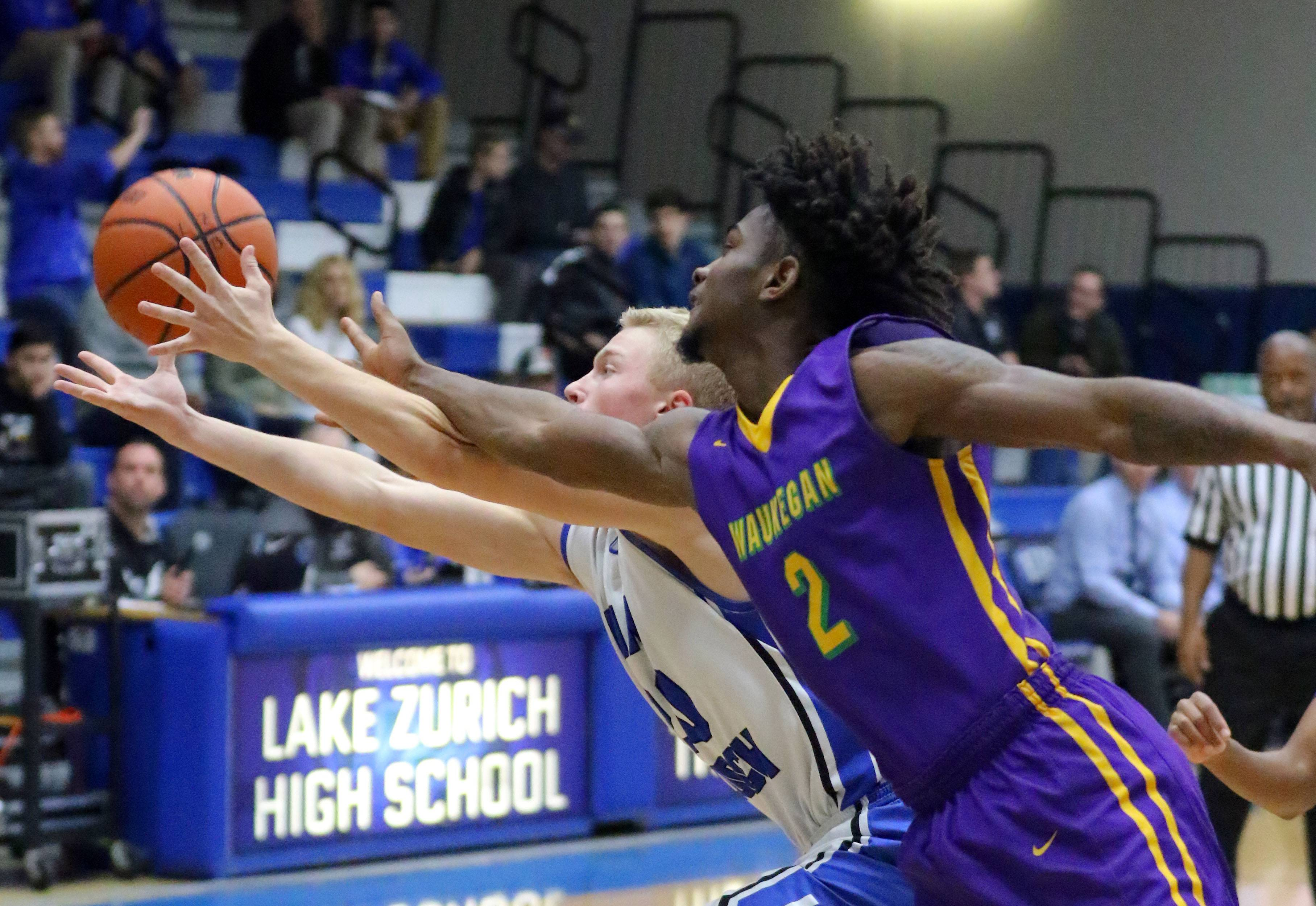 Lake Zurich's Joe Heffernan, left, and Waukegan's Ja'Dyn Brown fight for a rebound Friday in Lake Zurich.