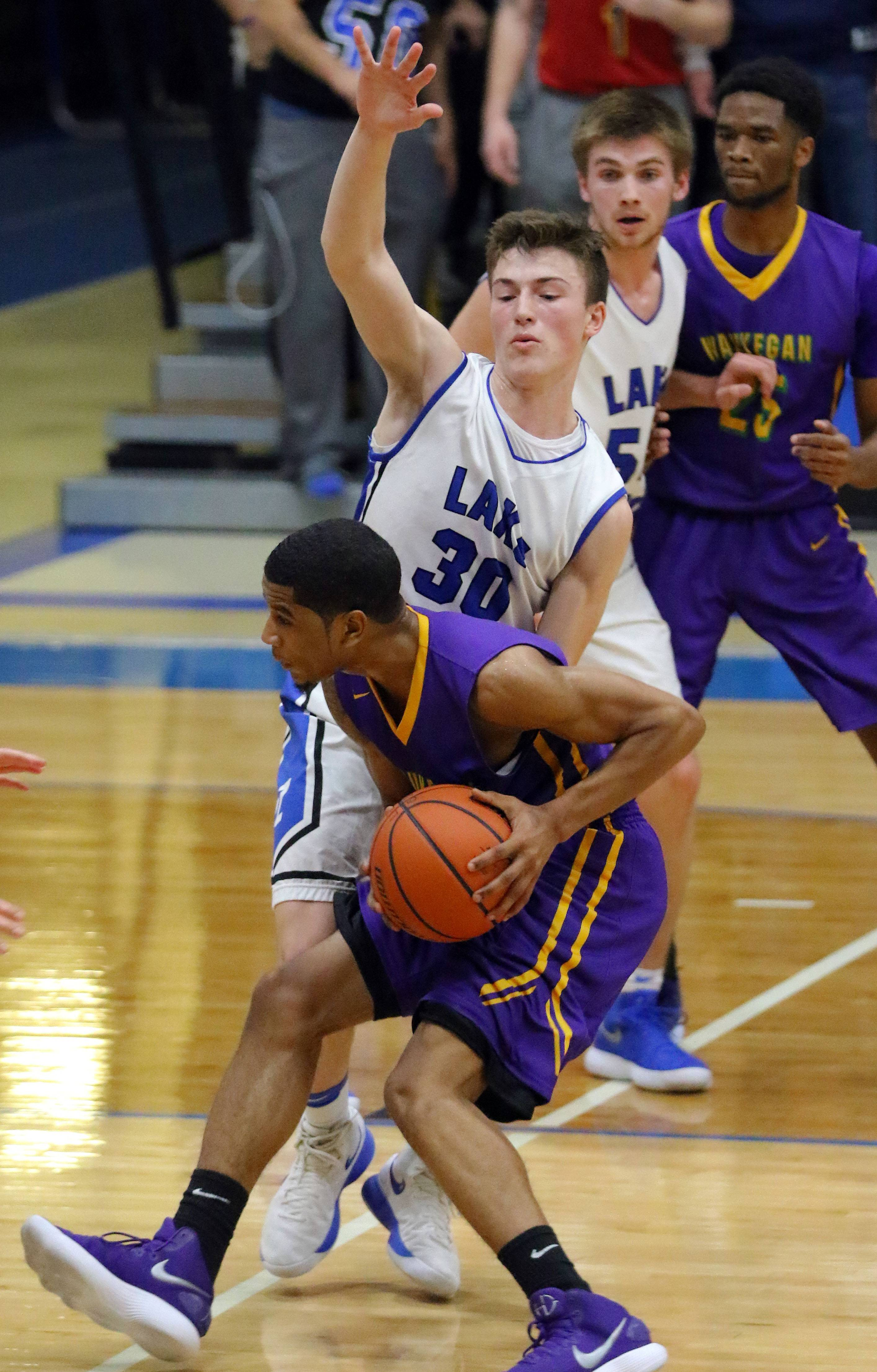 Lake Zurich's Will Tucker (30) defends against Waukegan's Jordan Brown on Friday in Lake Zurich.