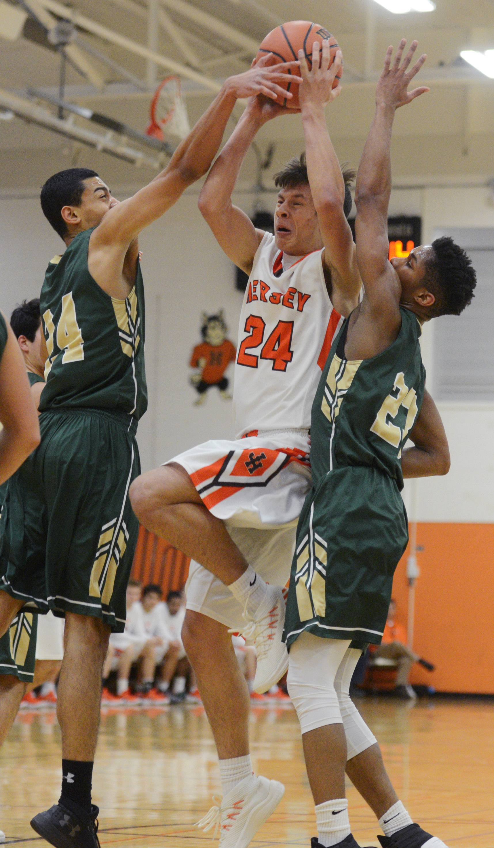 Hersey's Rocco Ronzio makes a move to the basket between Fremd's Bryce Hopkins, left, and Isaiah Turner during Tuesday's game in Arlington Heights.