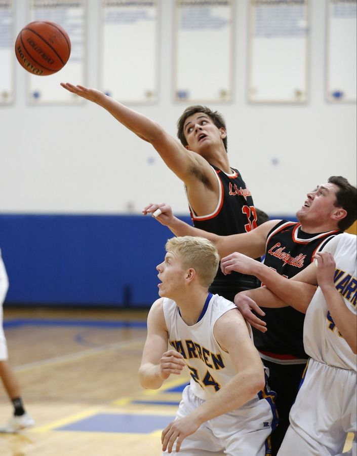 Libertyville's Travis Clark, top, and Brendan Cook battle for a rebound with Warren's Ryan Short during their game Tuesday night in Gurnee.