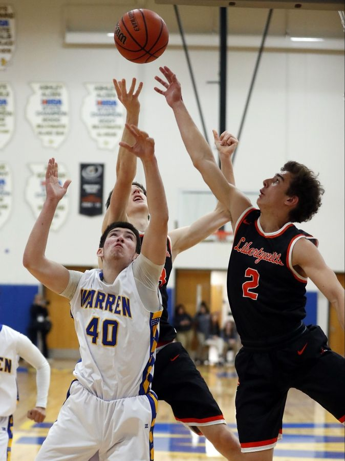 Warren's Adnan Sarancic (40) fights for a rebound with Libertyville's Brian Wilterdink (2) and Drew Peterson on Tuesday night in Gurnee.