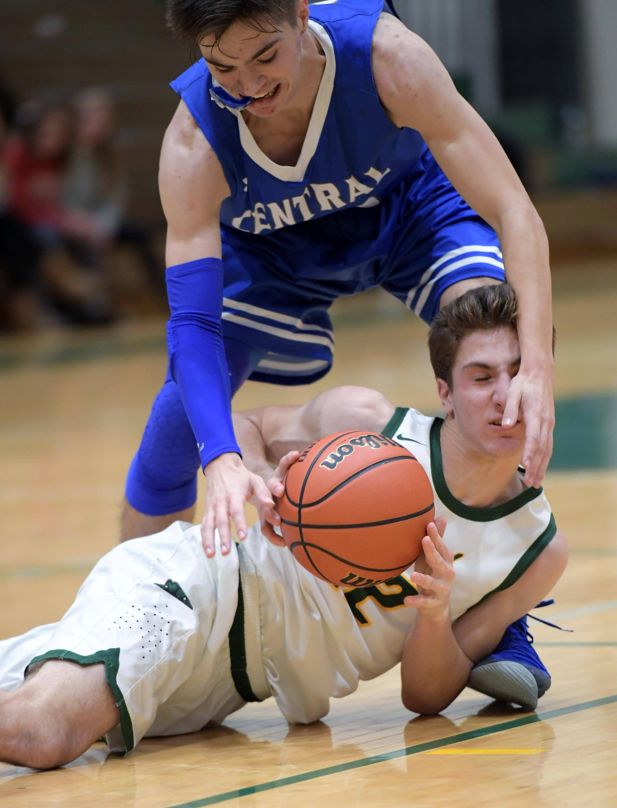 Burlington Central's Michael Kalusa reaches for the ball as Crystal Lake South's Ryan Lawson falls to the hardwood Wednesday in Crystal Lake.