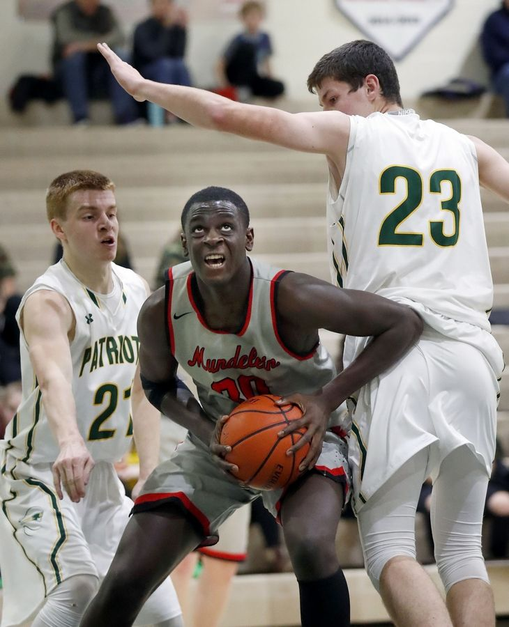 Mundelein's Chibuike Ebube splits Stevenson's Jackson Qualley, left, and Nick Bonk (23) on Friday night in Lincolnshire.