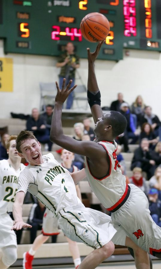 Mundelein's Chibuike Ebube, right, drives on Stevenson's Matt Ambrose on Friday night in Lincolnshire.