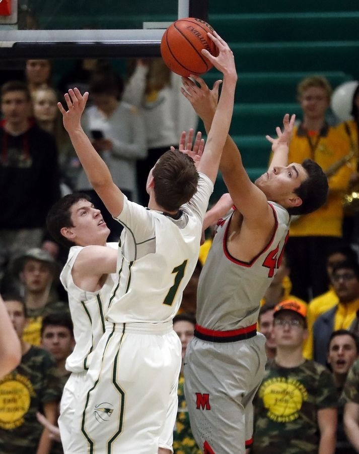 Stevenson's Nick Bonk, left, and Matthew Ambrose battle for a rebound with Mundelein's Andrew Silva, right, on Friday night in Lincolnshire.