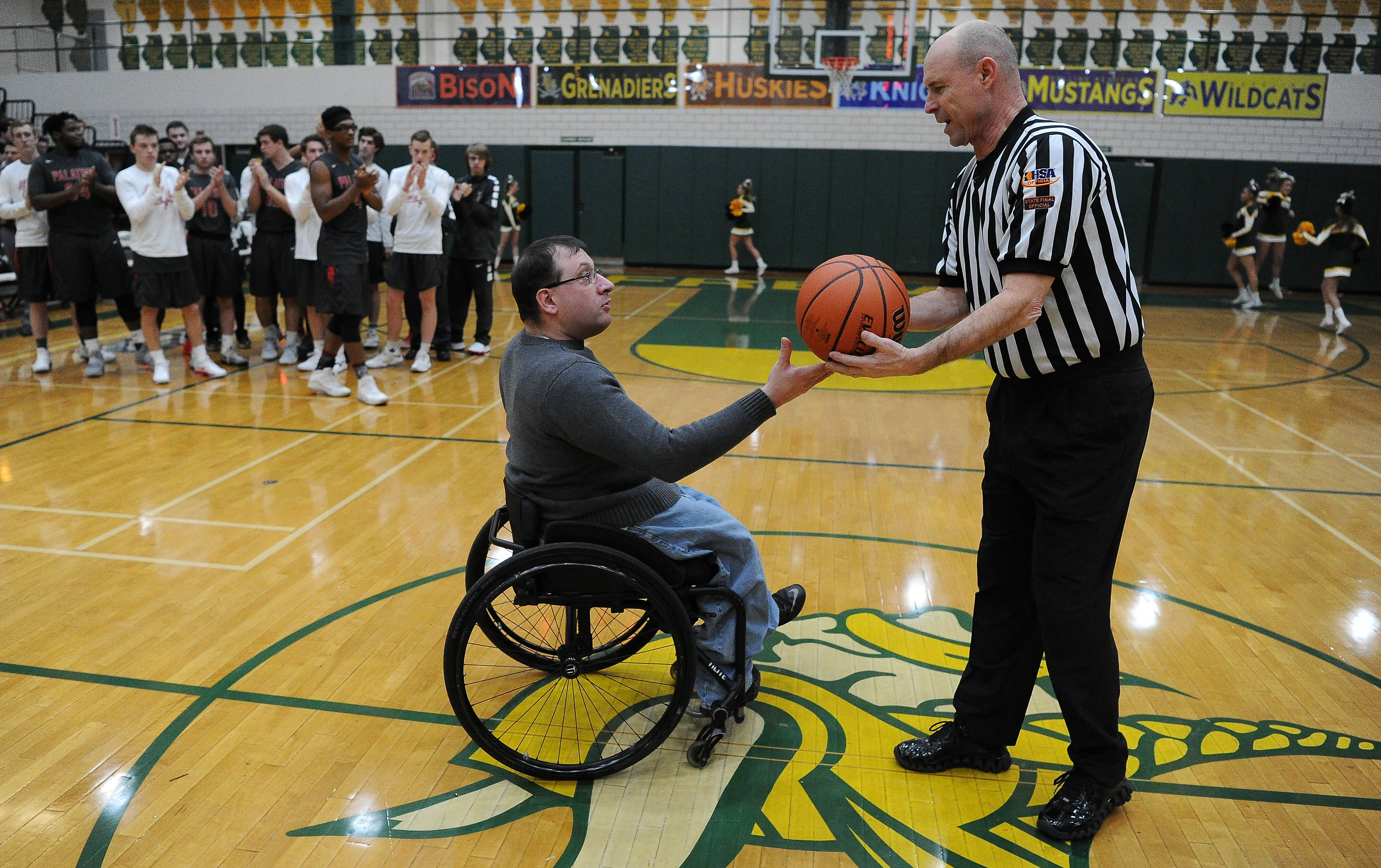 Jonathan Cregier presents the game ball to referee Tom Huster of Elmhurst in honor of his father, the late Ron Cregier, who was a longtime assistant coach for Fremd's basketball program. The presentation was at the boys varsity basketball game between Fremd and visiting Palatine.